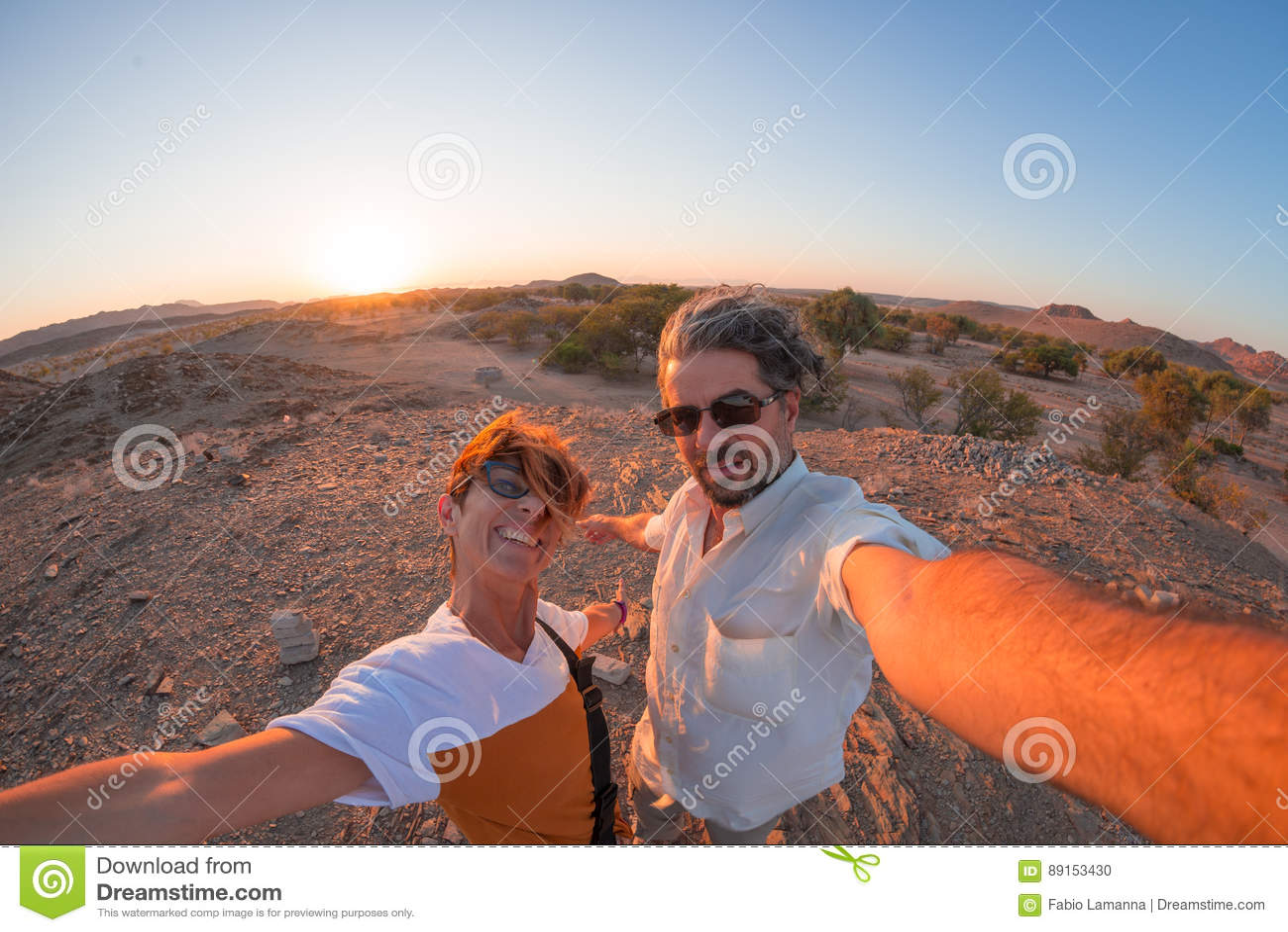 Glimlachend volwassen paar die selfie in de Namib-woestijn, het Nationale Park van Namib Naukluft, hoofdreisbestemming in Namibië