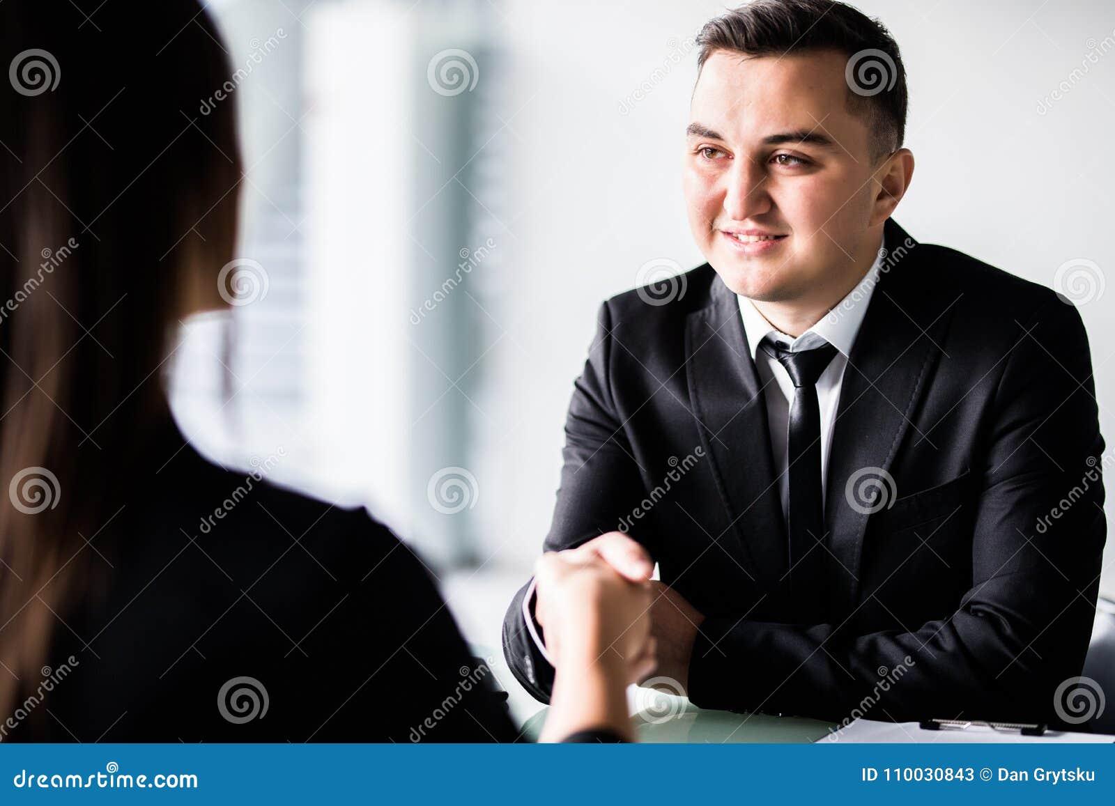 Glimlachend vriendschappelijke zakenman het schudden handen met vrouwenzitting bij bureau, keurde de holding onderhandelingsdocum