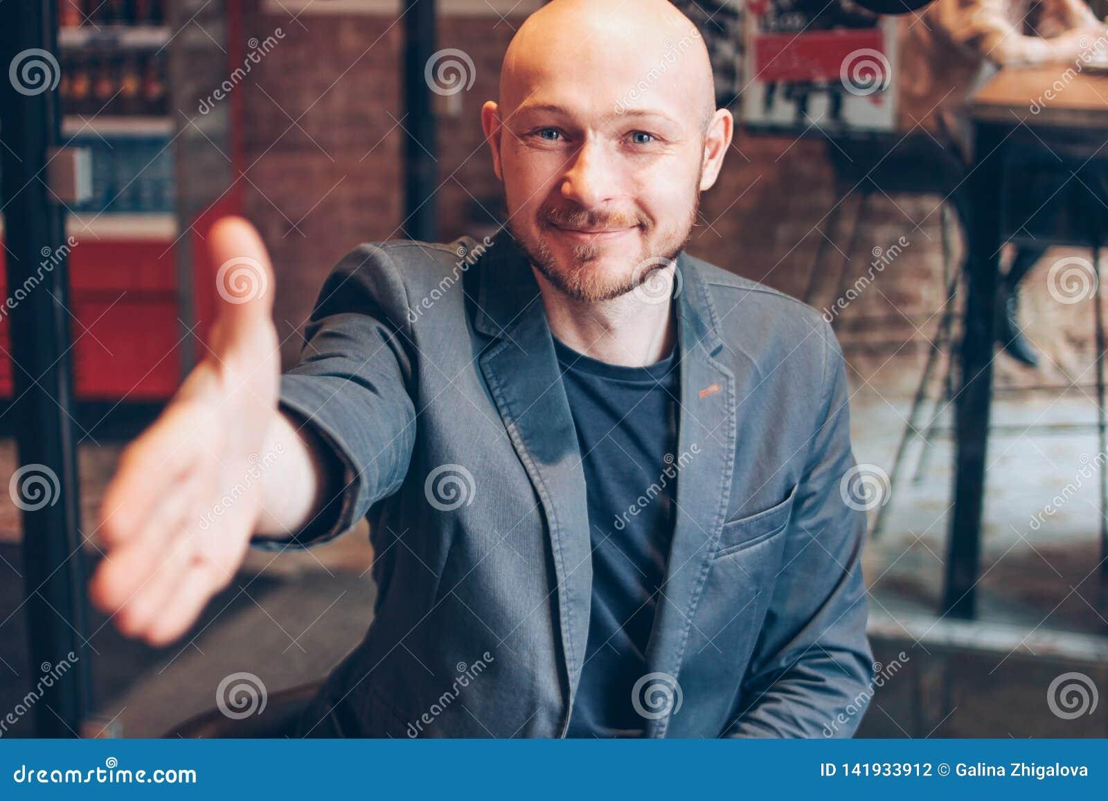 Glimlachende aantrekkelijke volwassen succesvolle kale gebaarde mens in kostuum met laptop die handdruk, hand geven die van hulp,