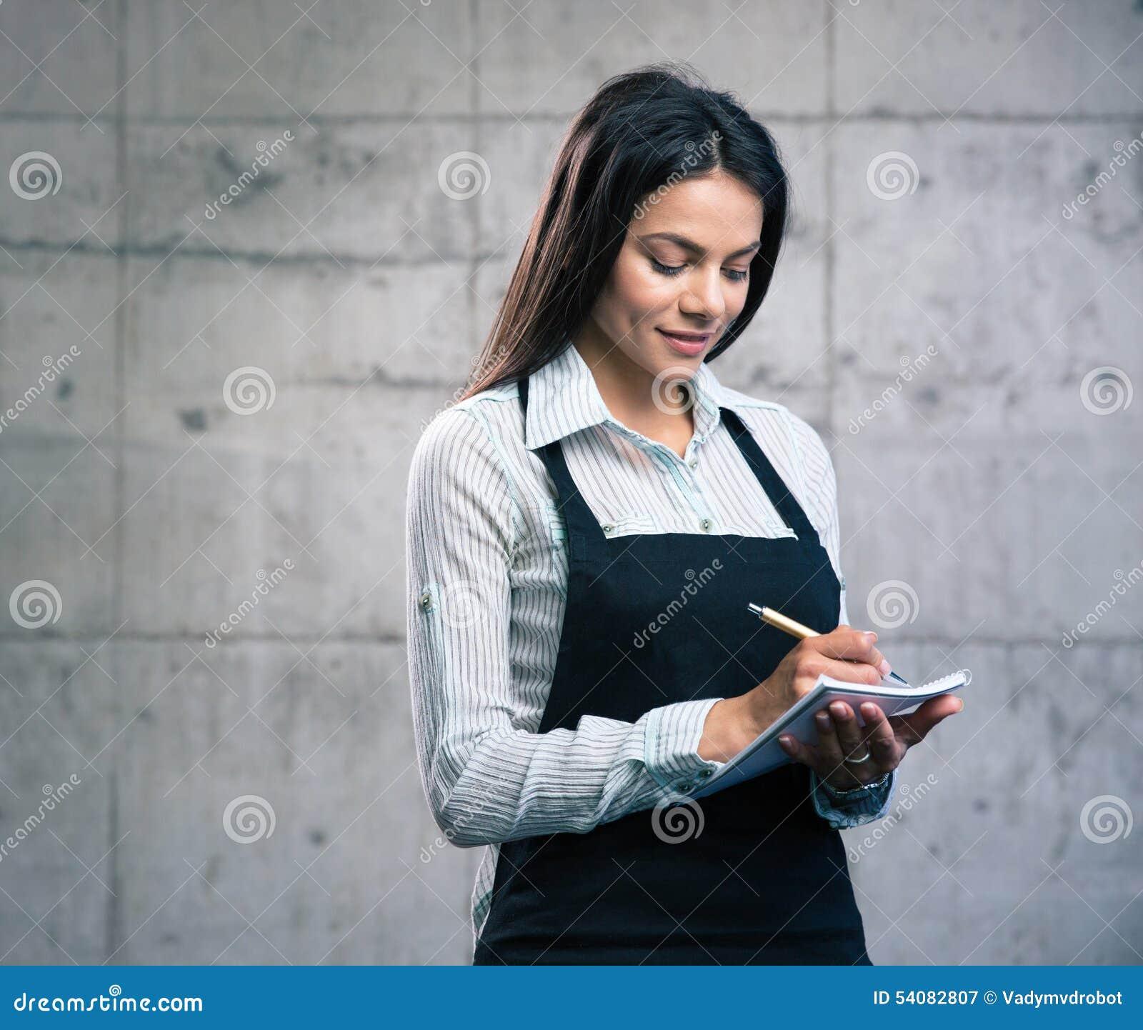Glimlachende aantrekkelijke vrouwelijke kelner in schort