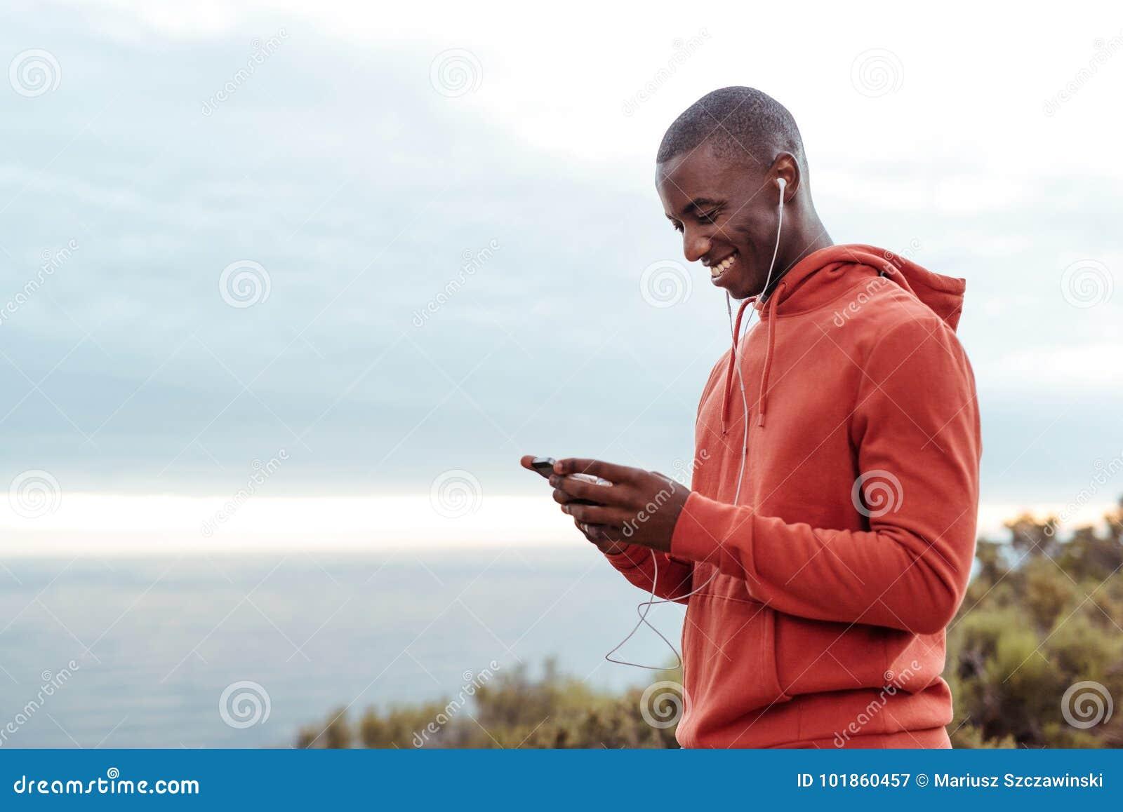 Glimlachende Afrikaanse mens die aan muziek luisteren terwijl uit het aanstoten