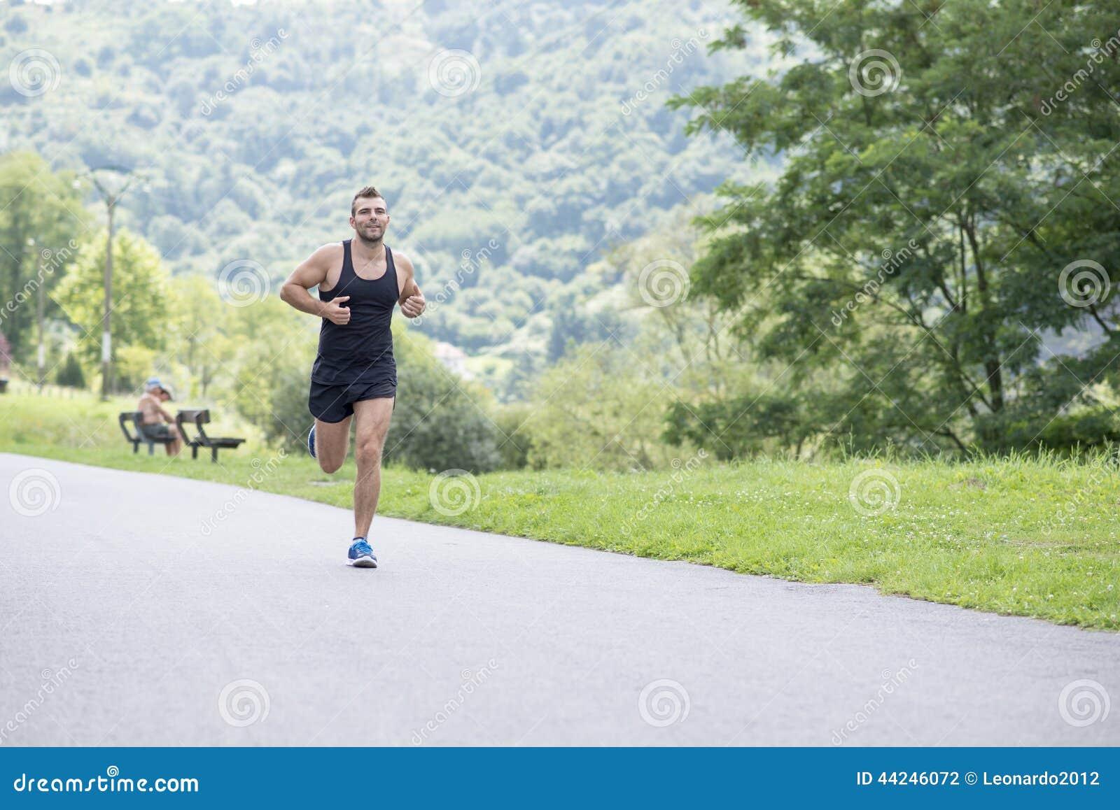 Glimlachende atletische mens die in het park lopen
