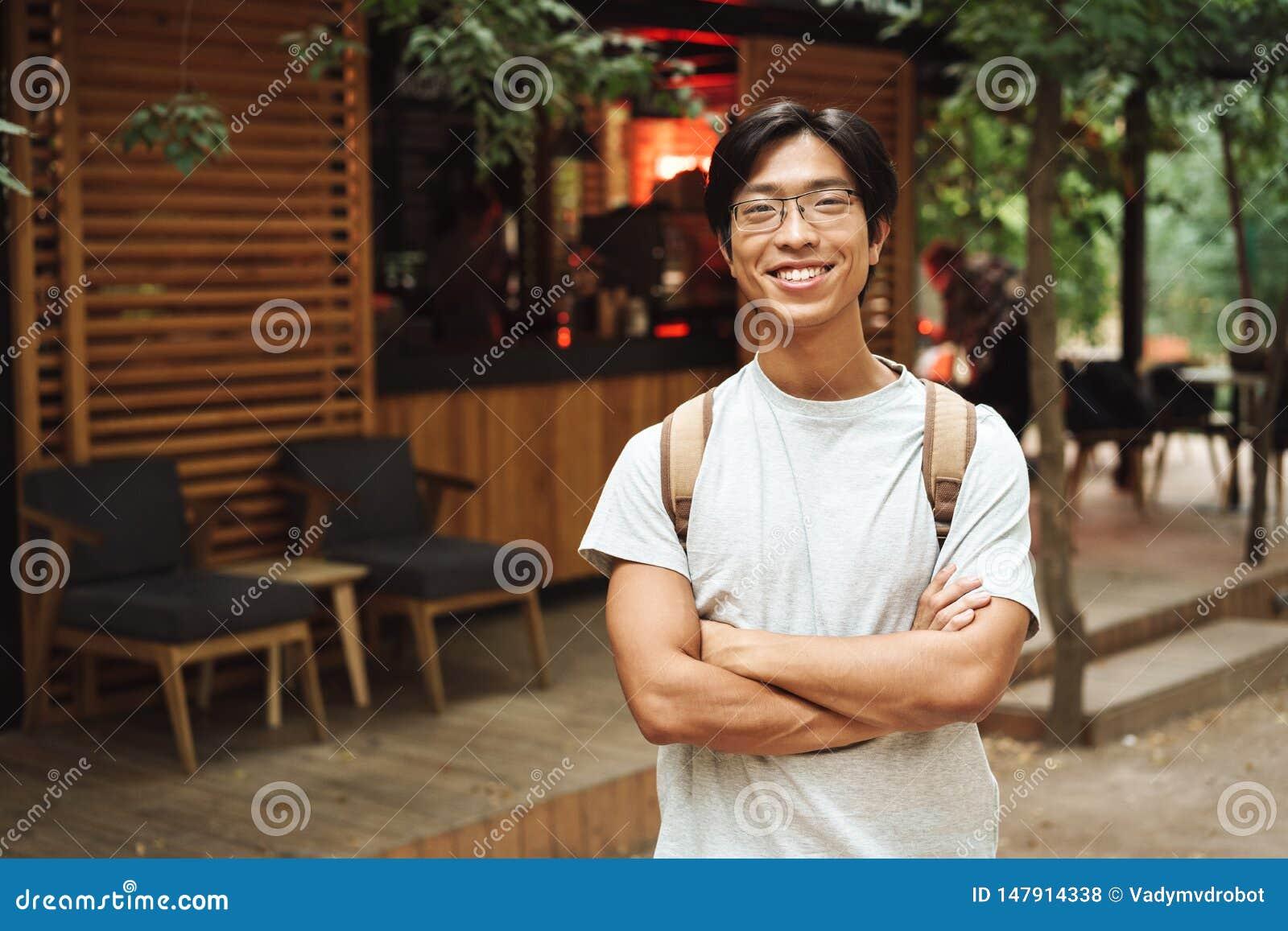Glimlachende Aziatische studentenmens die rugzak dragen
