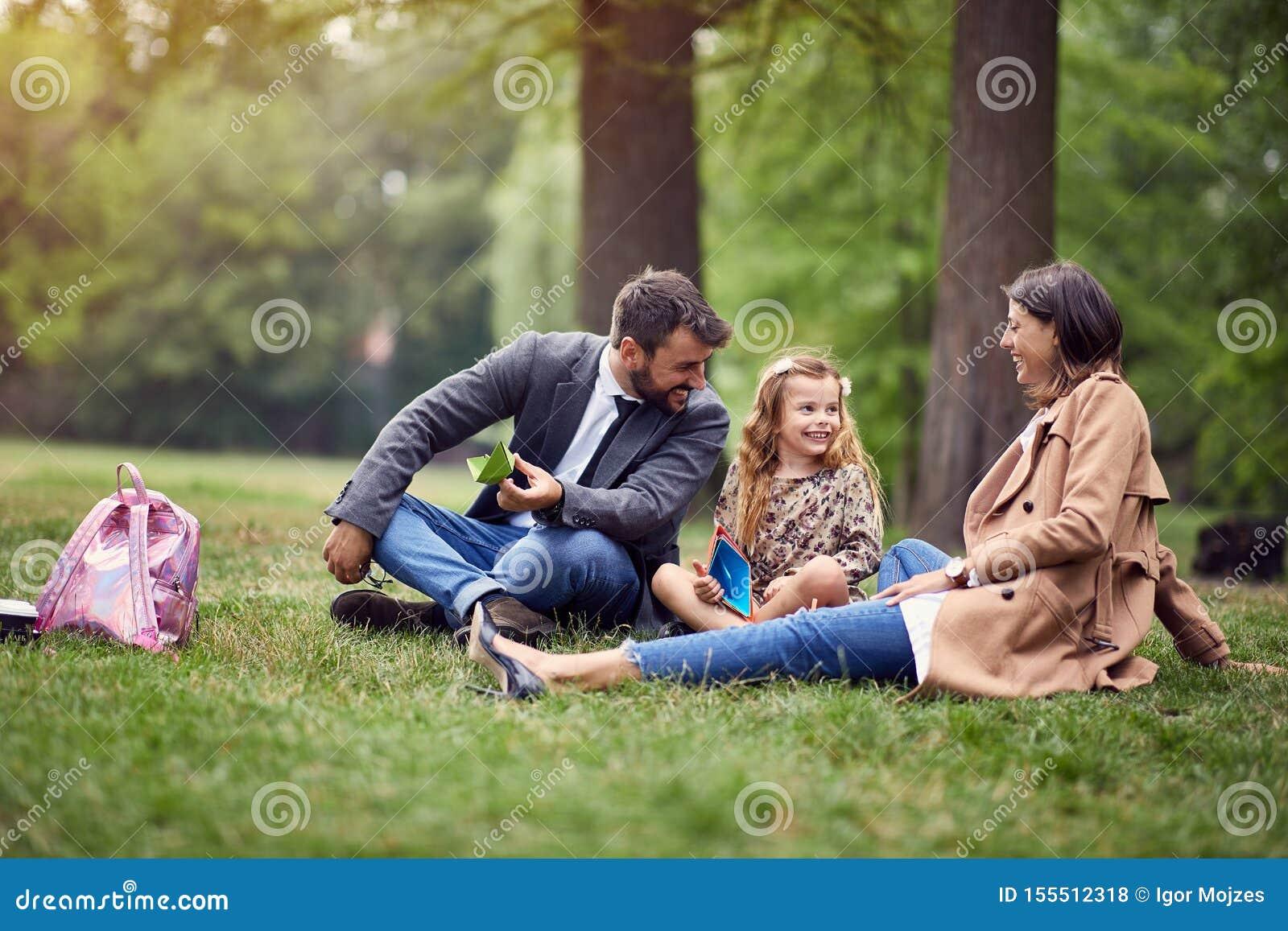 Glimlachende commerciële ouders met een jong geitje in park