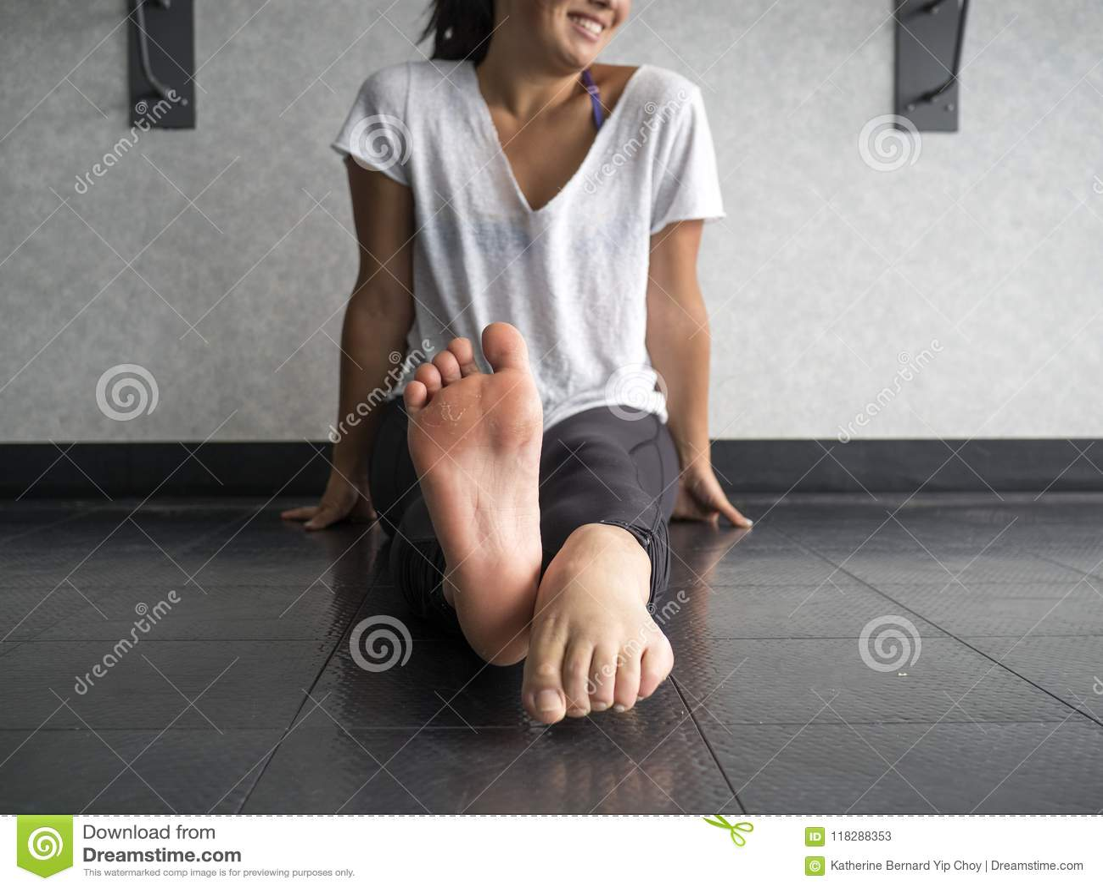 Glimlachende danser die haar voeten met het afwisselen opwarmen richtend en buigend