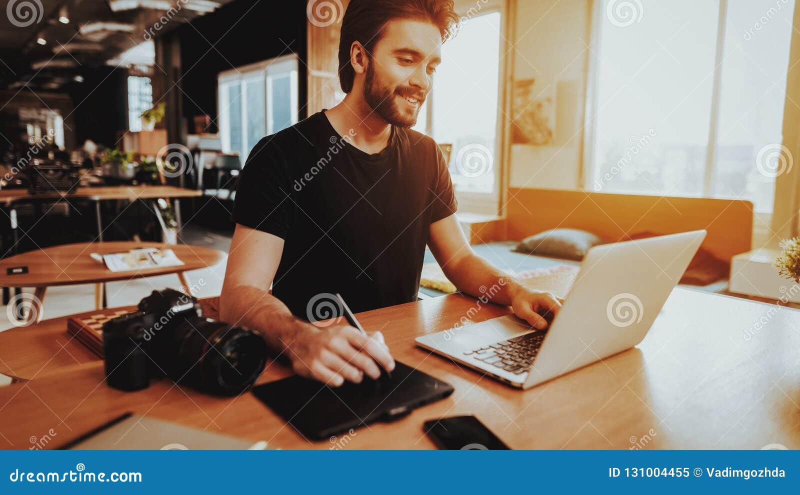 Glimlachende Grafische Ontwerper Works op Laptop binnen