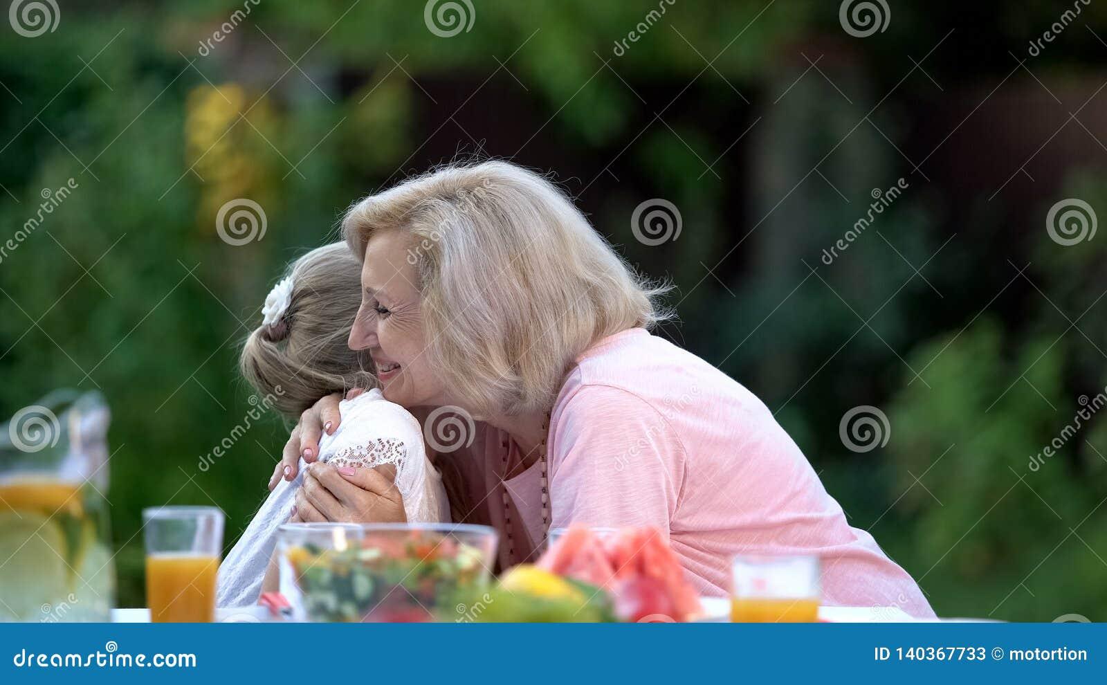Glimlachende grootmoeder die emotioneel kleine kleindochter, gelukemotie omhelzen
