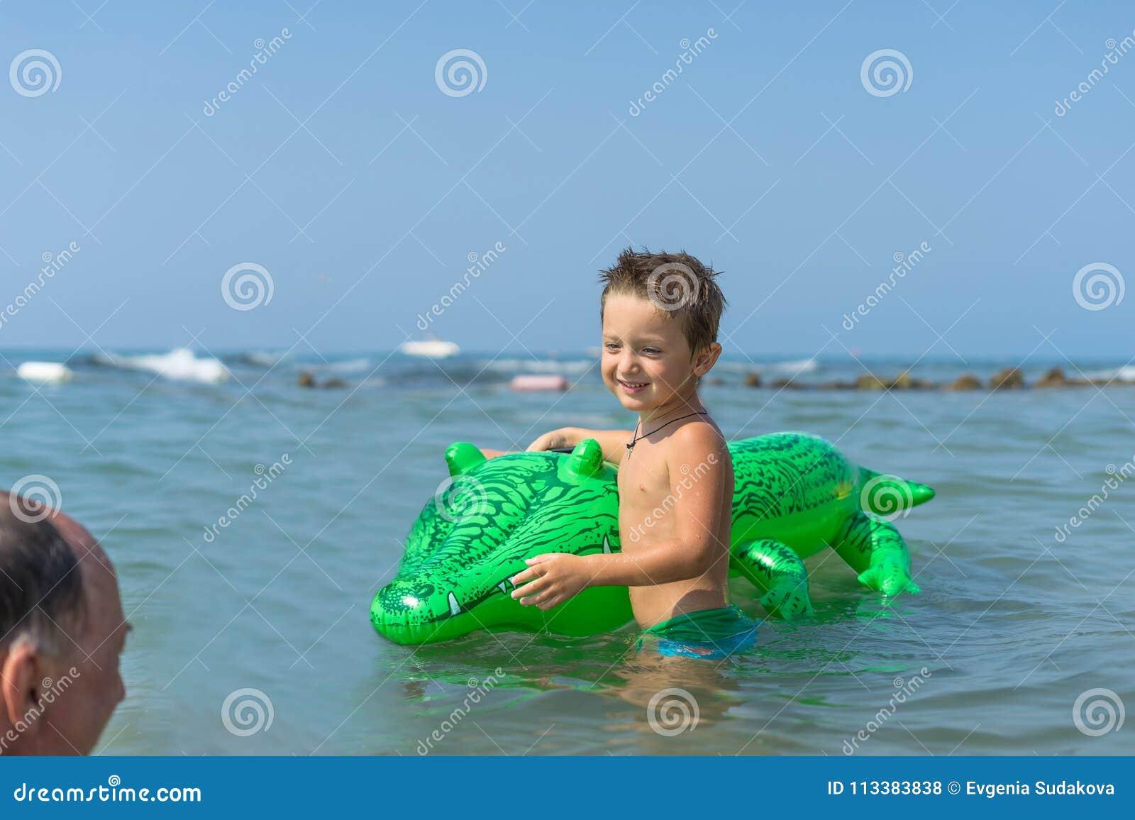 Glimlachende grootvader en kleinzoon die en in het zeewater spelen bespatten Portret van gelukkig weinig jong geitjejongen op het