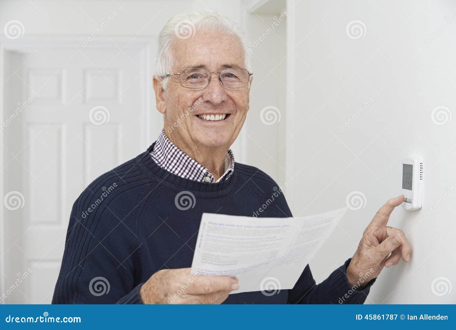 Glimlachende Hogere Mens met Bill Adjusting Central Heating Thermosta
