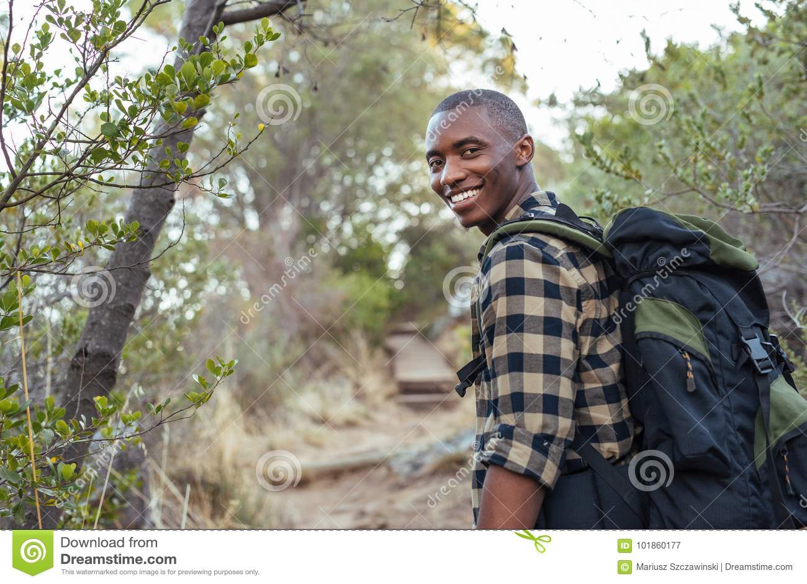 Glimlachende jonge Afrikaanse mens die in de heuvels wandelen
