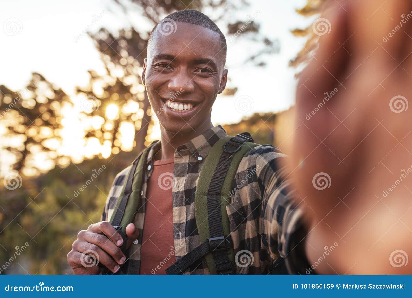 Glimlachende jonge Afrikaanse mens die selfies terwijl uit wandeling nemen