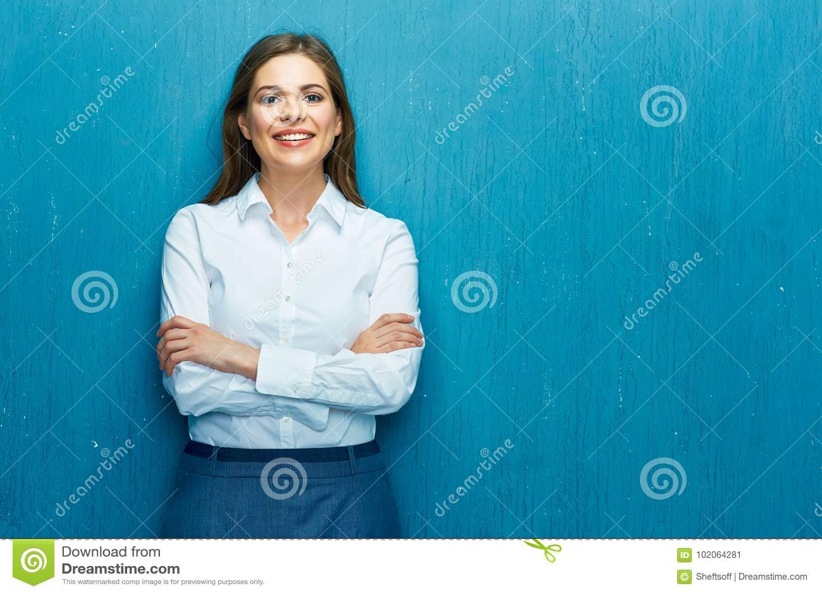 Glimlachende jonge bedrijfsvrouw tegen blauwe muur