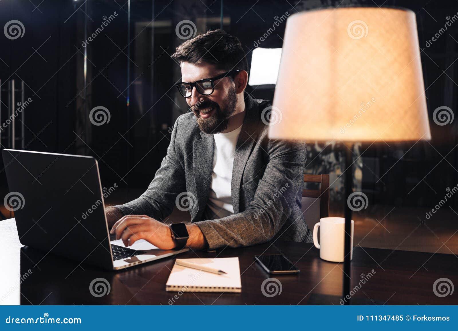 Glimlachende jonge gebaarde zakenman die aan eigentijds notitieboekje in zolderbureau bij nacht werken