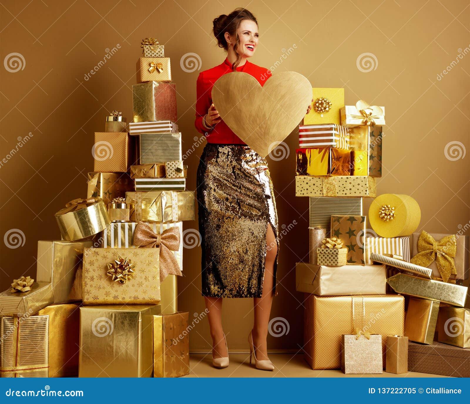 Glimlachende jonge klantenvrouw die met gouden hart opzij kijken