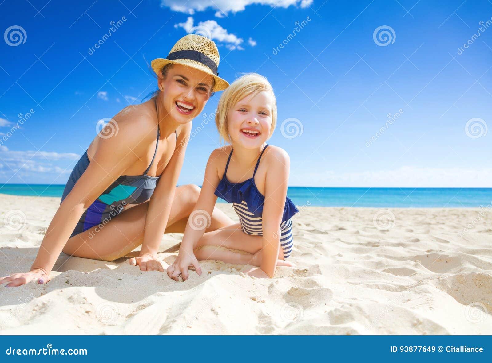 Glimlachende jonge moeder en dochter in swimwear op zeekust