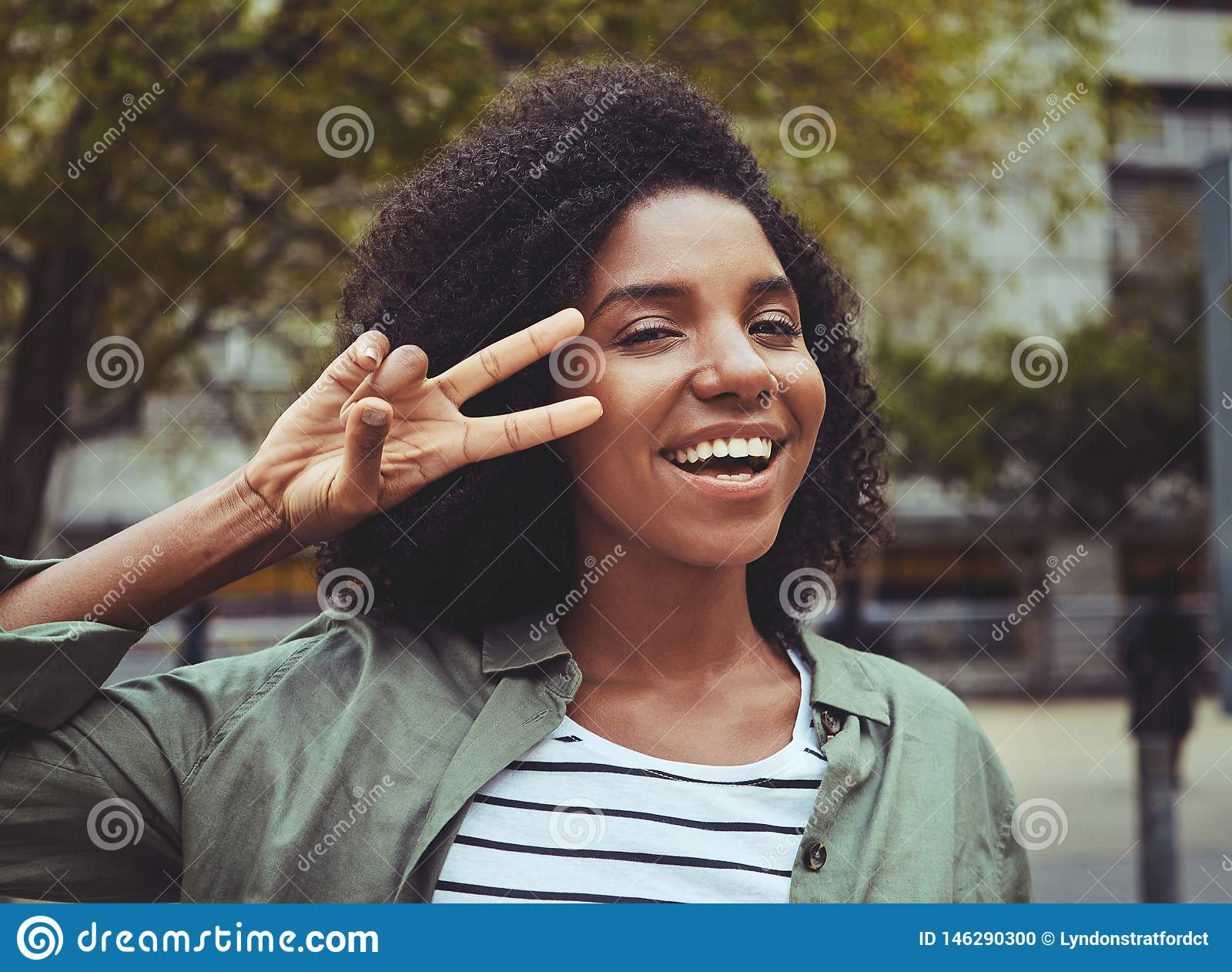 Glimlachende jonge vrouw die vredesteken tonen