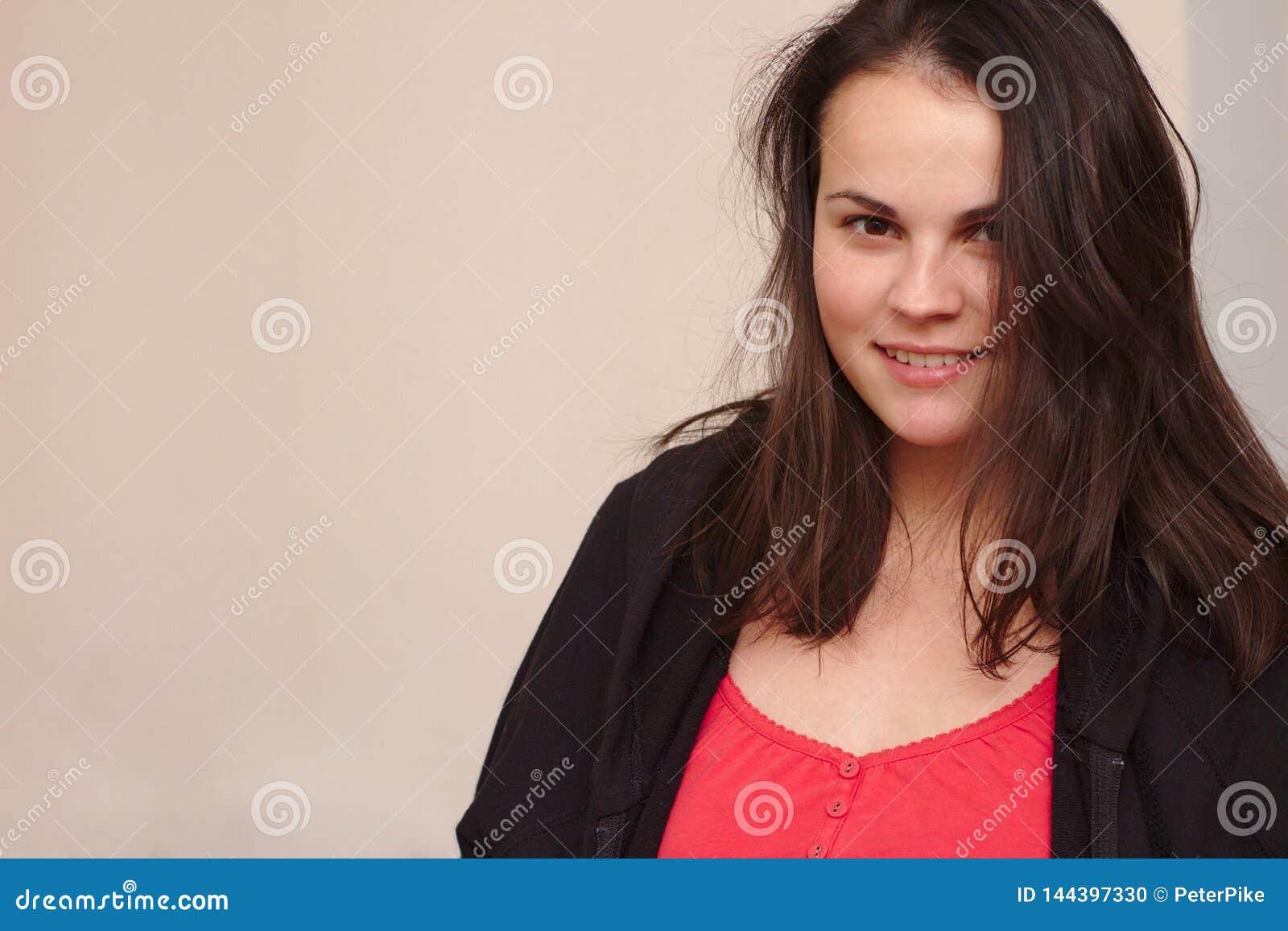 Glimlachende jonge vrouw in vrijetijdskleding Portret plus groottemodel op achtergrond