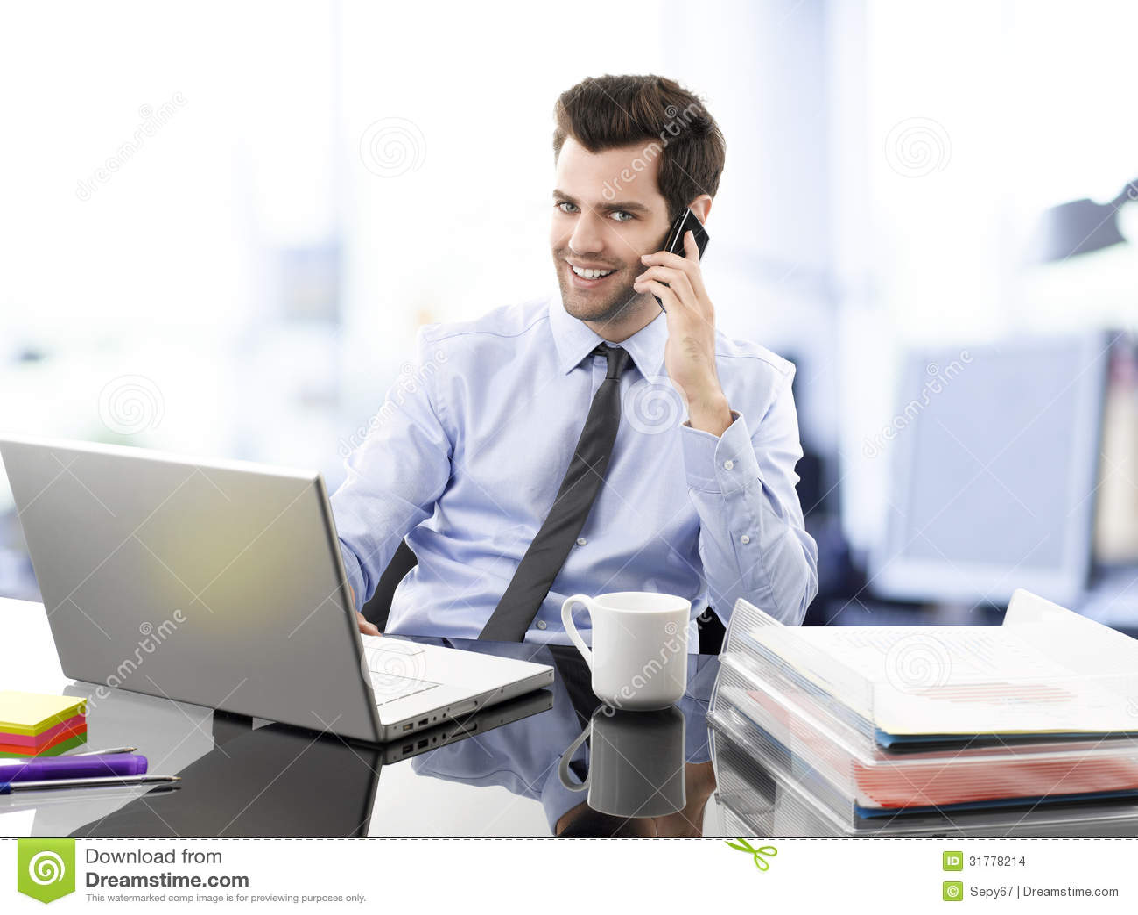 Glimlachende jonge zakenman die op mobiele telefoon for La oficina telefono