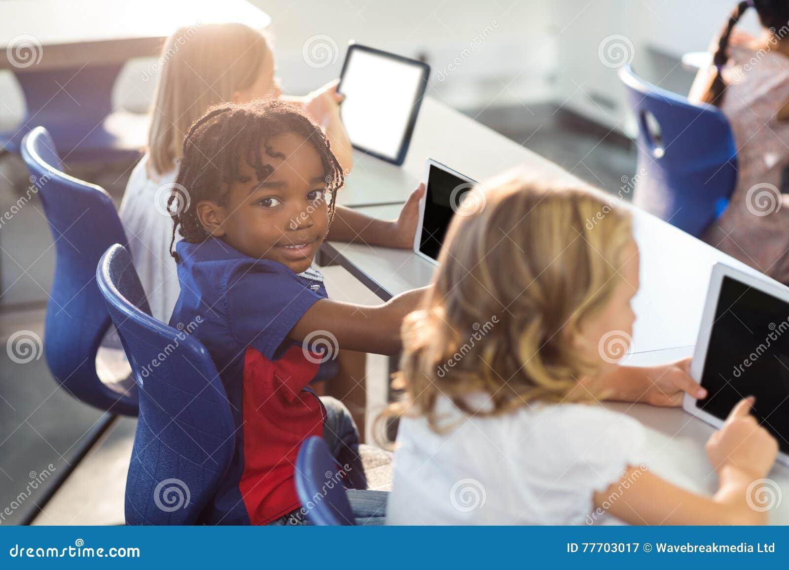 Glimlachende jongen met klasgenoten die digitale tablet gebruiken