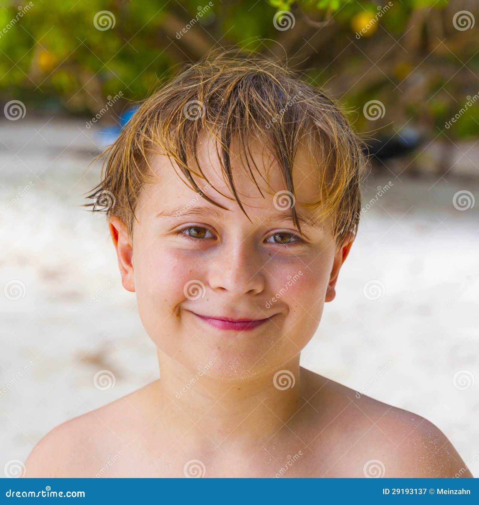 De Gelukkige Jonge Jongen Met Bruin Haar Geniet Van Het Strand Stock Afbeelding - Afbeelding
