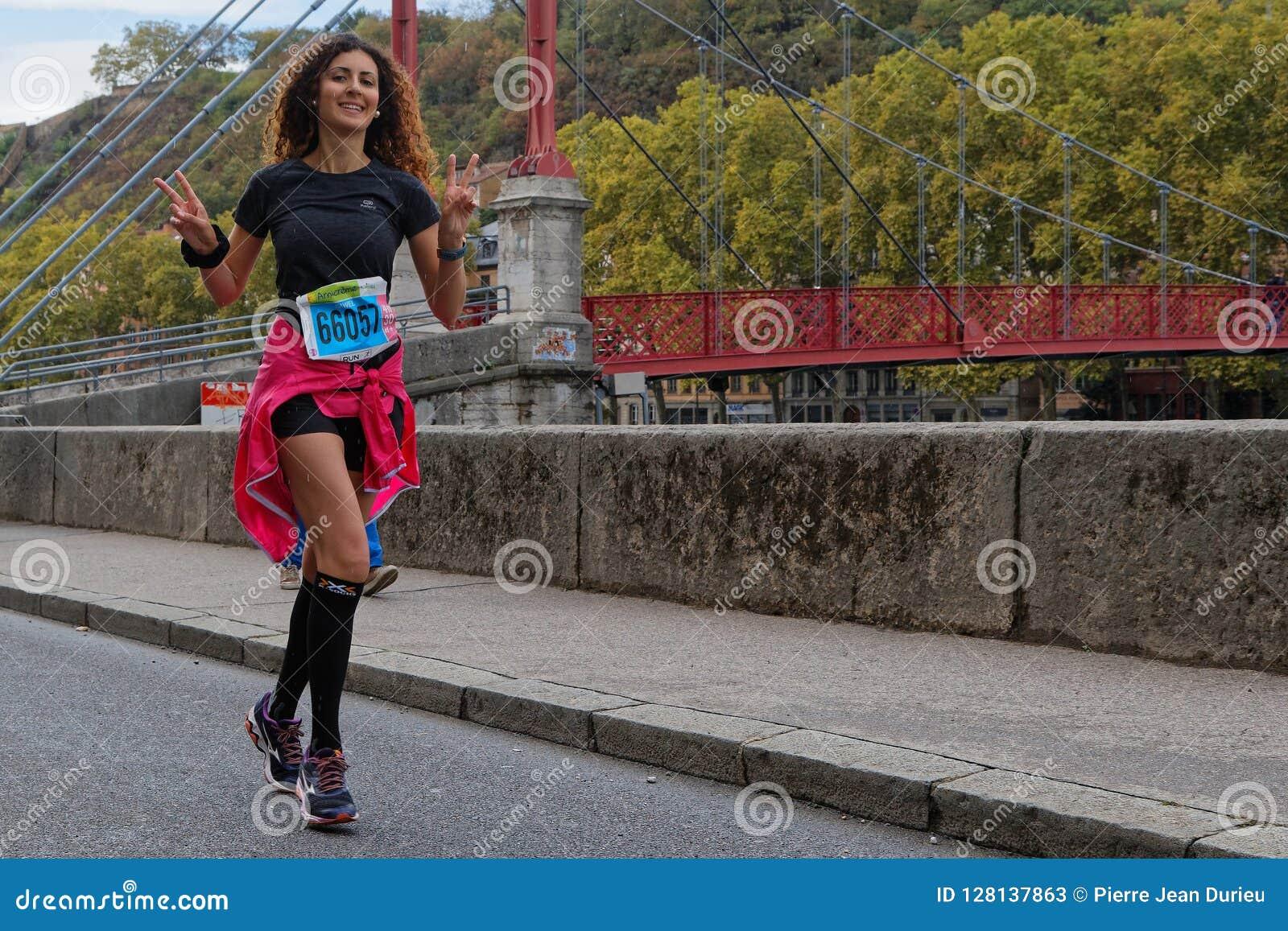 Glimlachende lopende jonge vrouw in Lyon