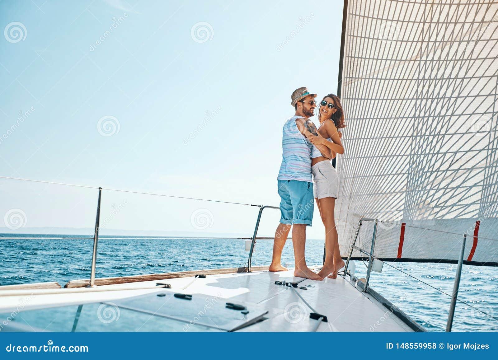 Glimlachende man en vrouw die op vakantie reizen die bij het oceaan Romaans genieten van van de open zee varen