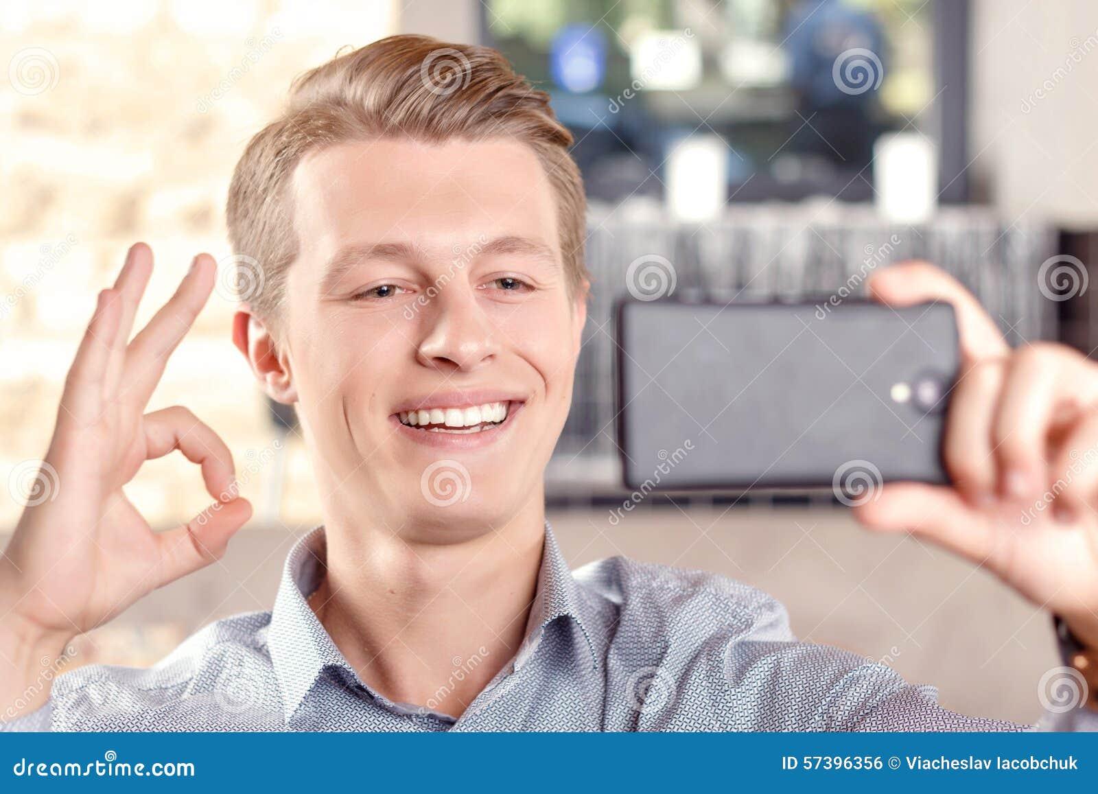 Glimlachende mens die selfie in koffie doen
