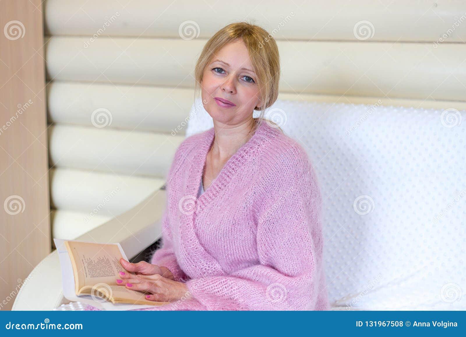 Glimlachende middenleeftijdsvrouw die een boek thuis lezen