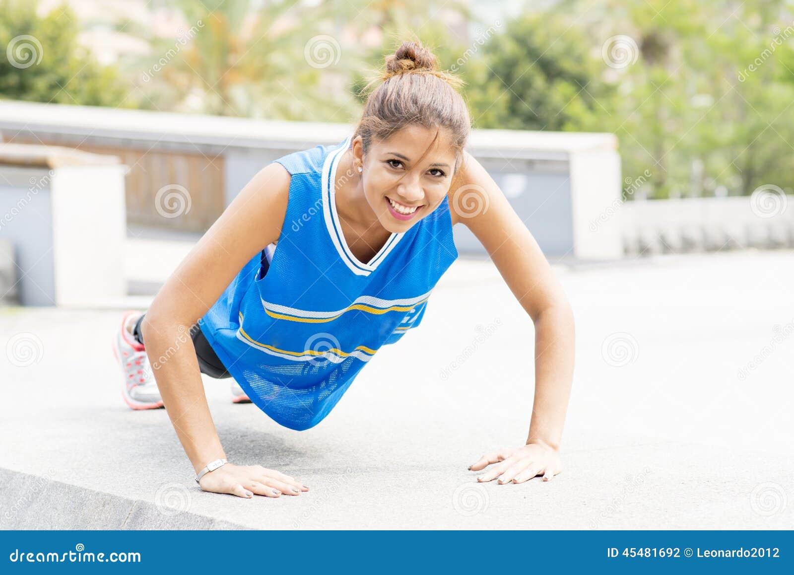 Glimlachende mooie atletische vrouw die opdrukoefeningen in de straat doen