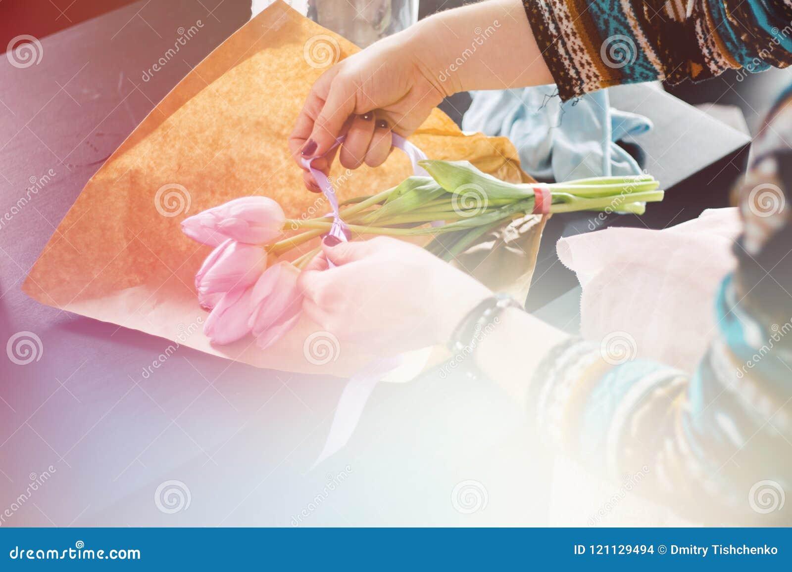 Glimlachende mooie jonge vrouwenbloemist die installaties in bloemwinkel schikken, het lichte stemmen