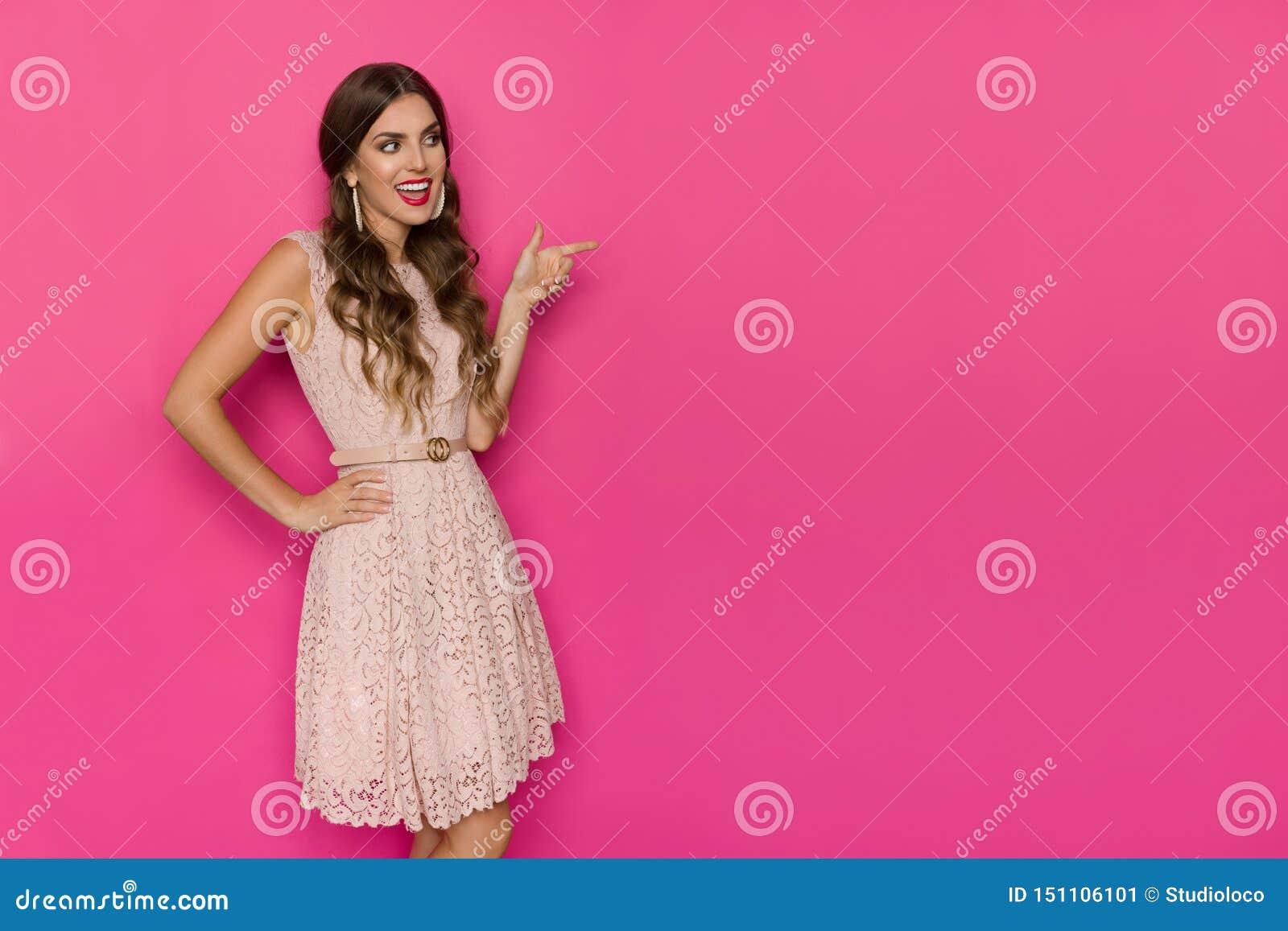 Glimlachende Mooie Vrouw in Beige Kant Mini Dress Is Looking Away, het Richten en het Spreken