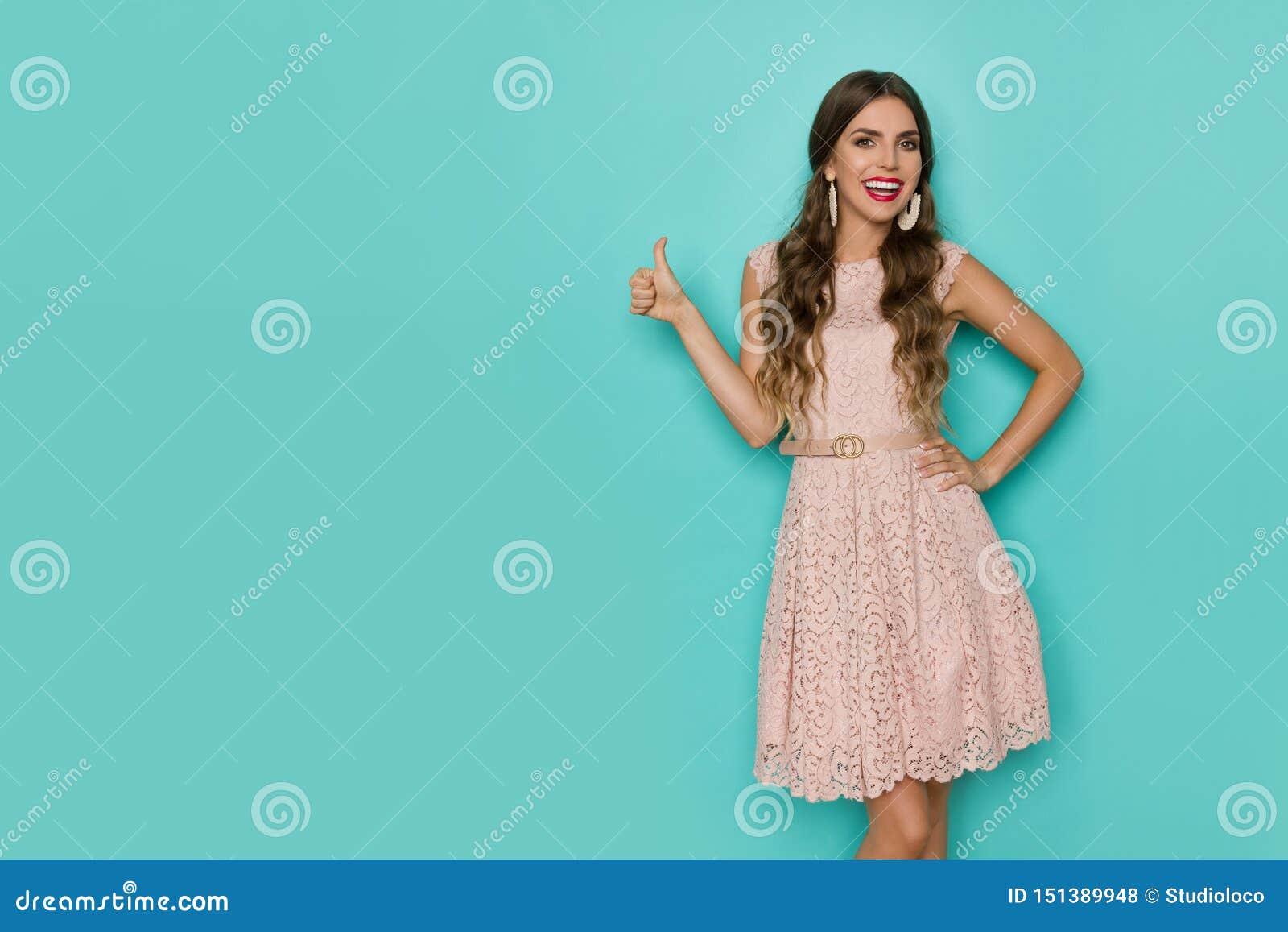 Glimlachende Mooie Vrouw in Beige Kant Mini Dress Is Showing Thumb omhoog