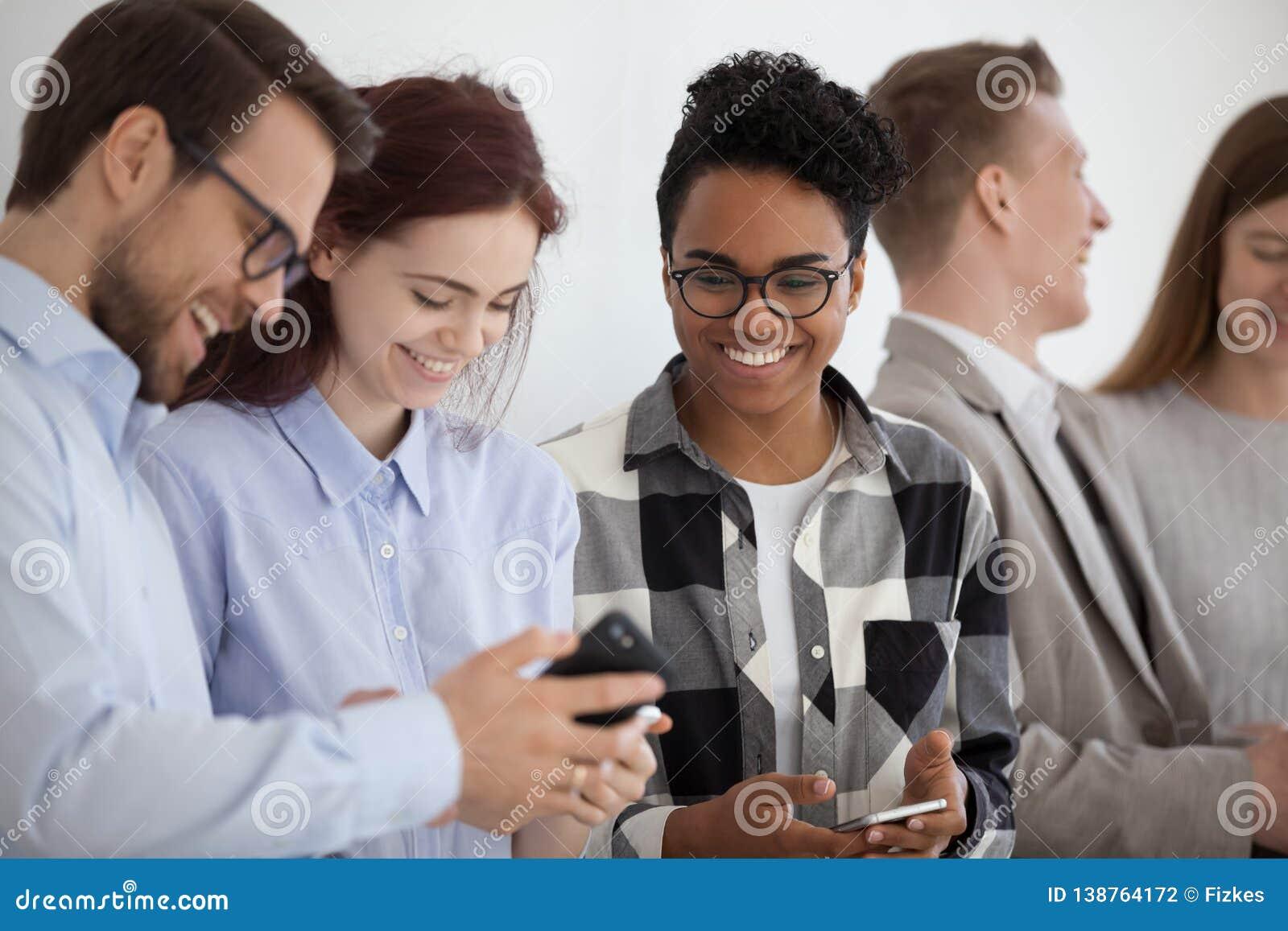 Glimlachende multi-etnische mensen die telefoons houden die pret met mobiele apparaten hebben