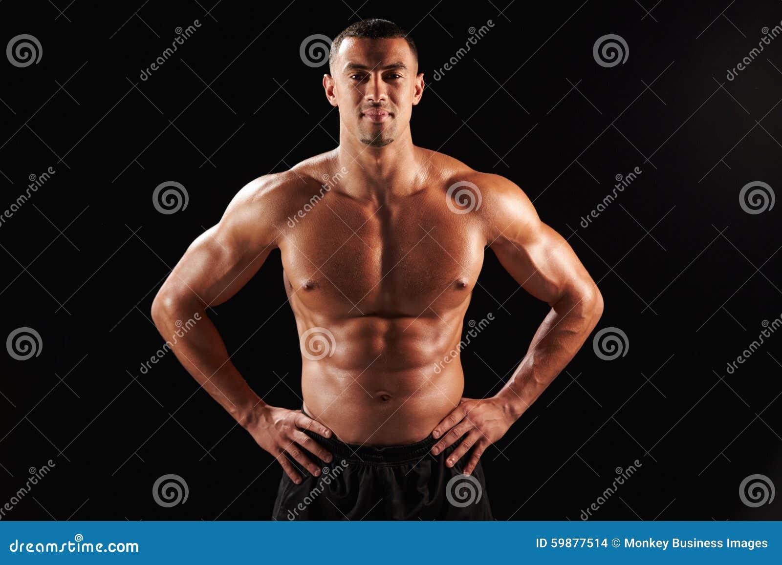 Glimlachende naakte chested mannelijke lichaamsbouwer met handen op heupen
