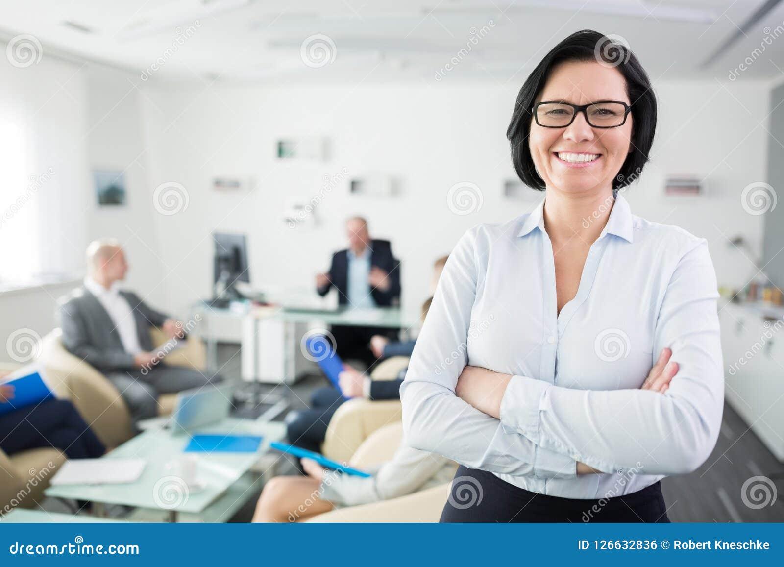 Glimlachende Onderneemster Standing Arms Crossed in Bureau