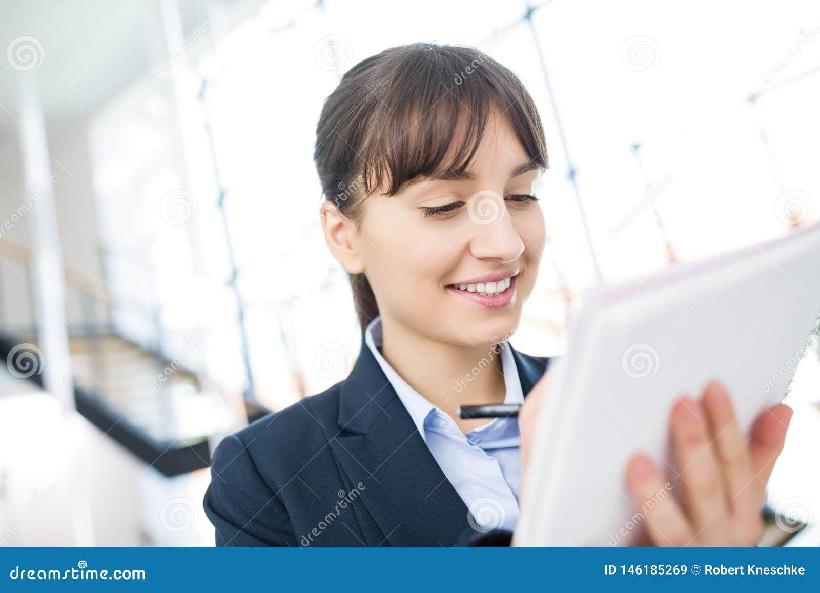 Glimlachende Onderneemster Writing On Document in Bureau