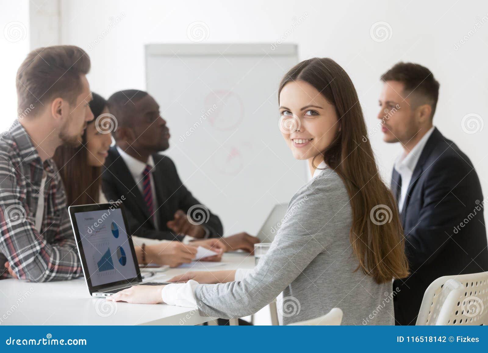 Glimlachende onderneemsterberoeps of intern die camera a bekijken
