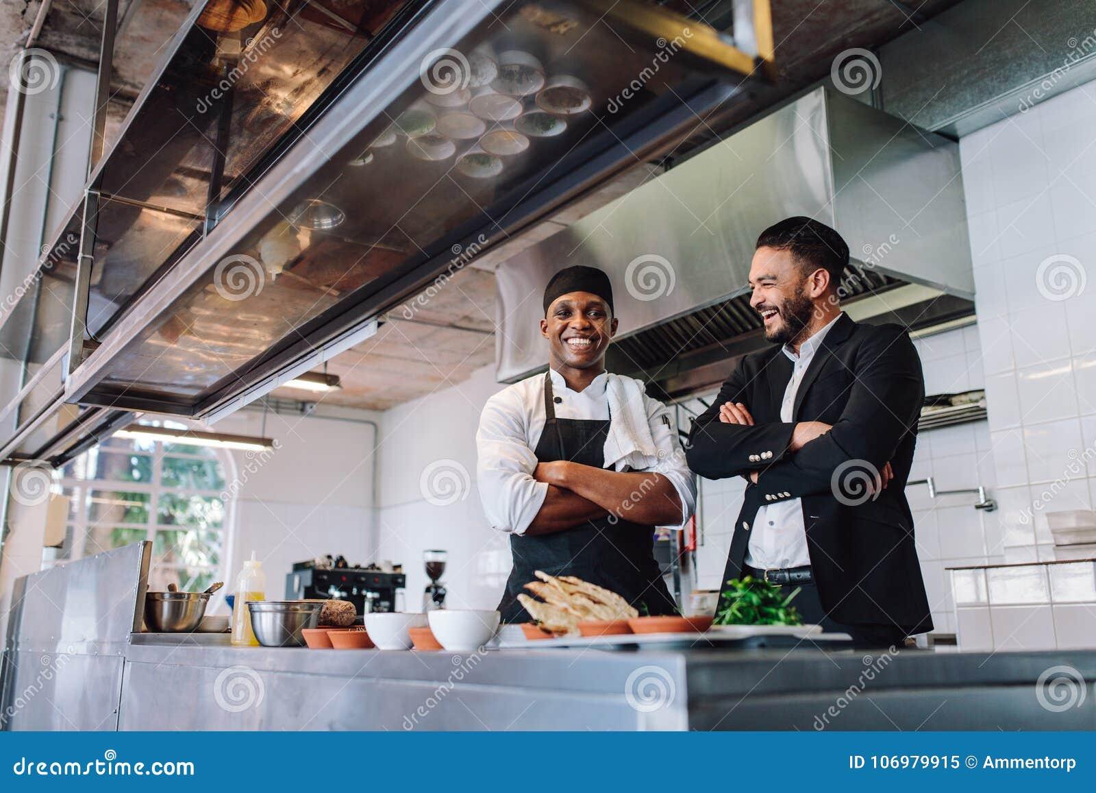 Glimlachende restauranteigenaar en chef-kok die zich in keuken bevinden