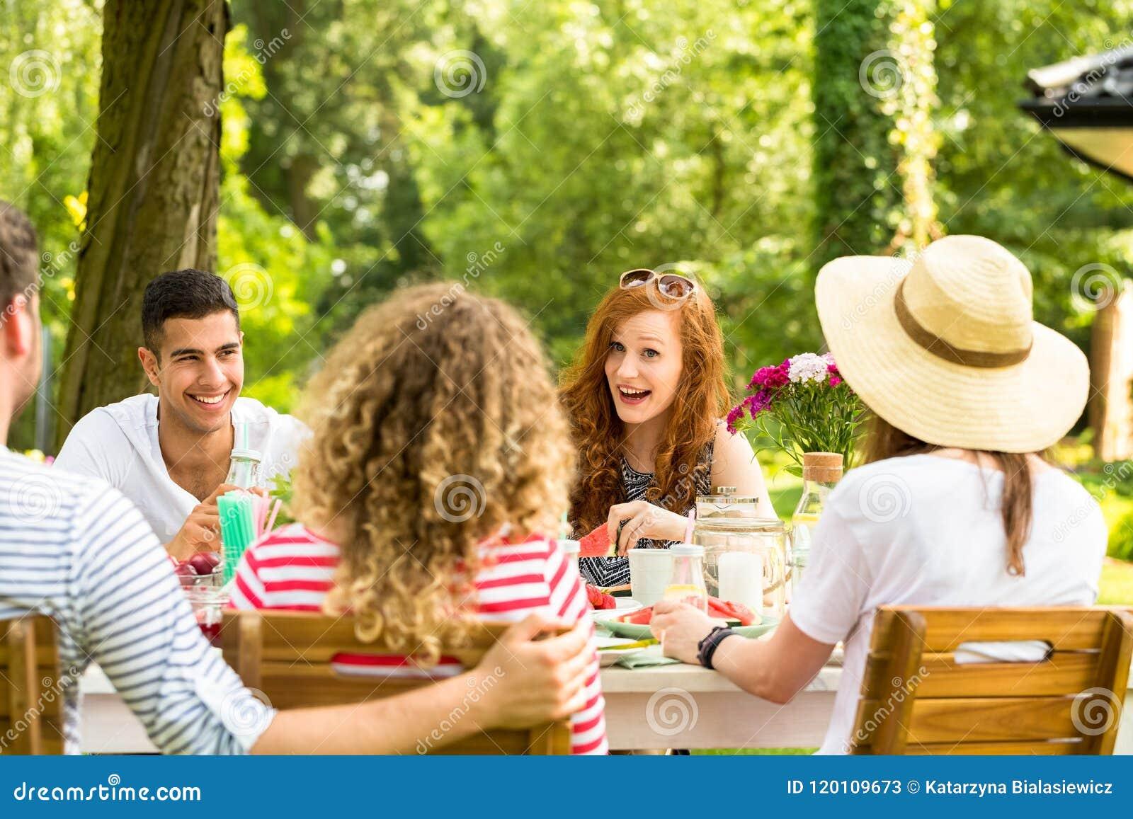 Glimlachende roodharige vrouw die pret hebben tijdens tuinpartij met mul