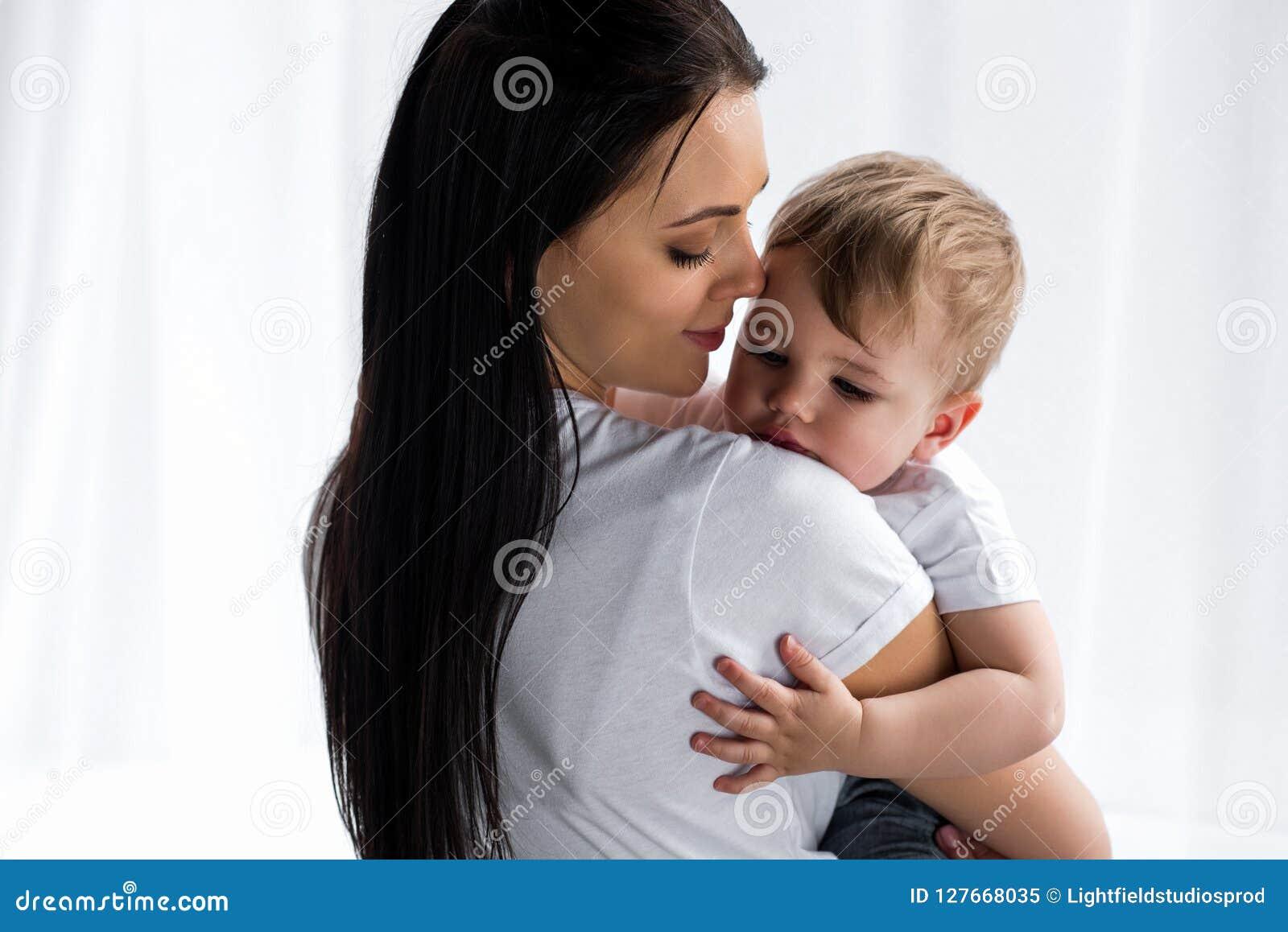Glimlachende tedere moeder die leuke babyjongen houden