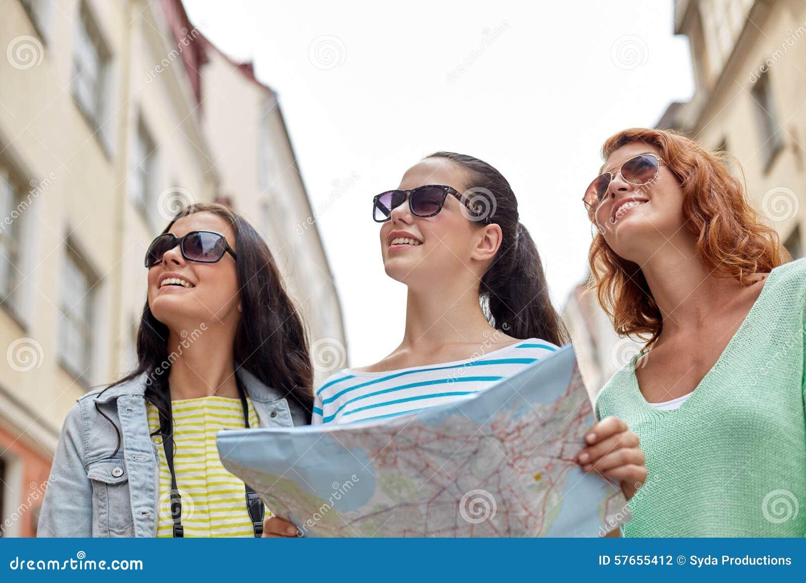 Glimlachende tieners met kaart en camera in openlucht