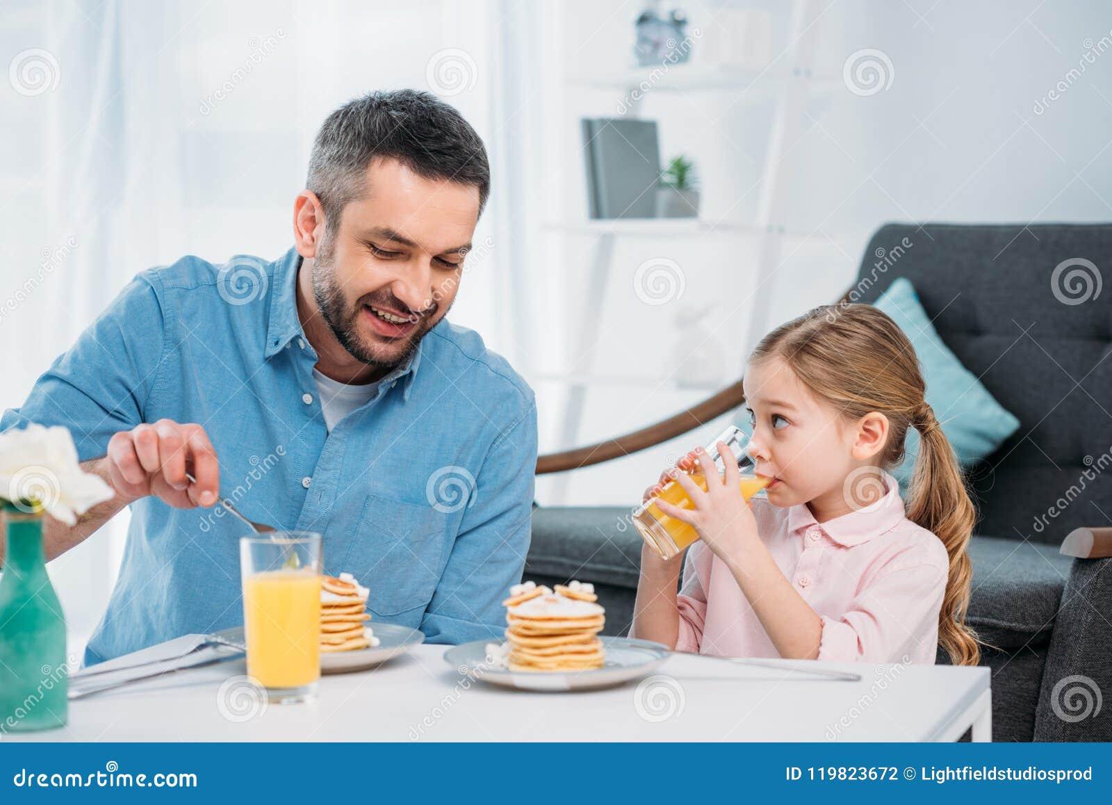 Glimlachende vader en weinig dochter die ontbijt hebben