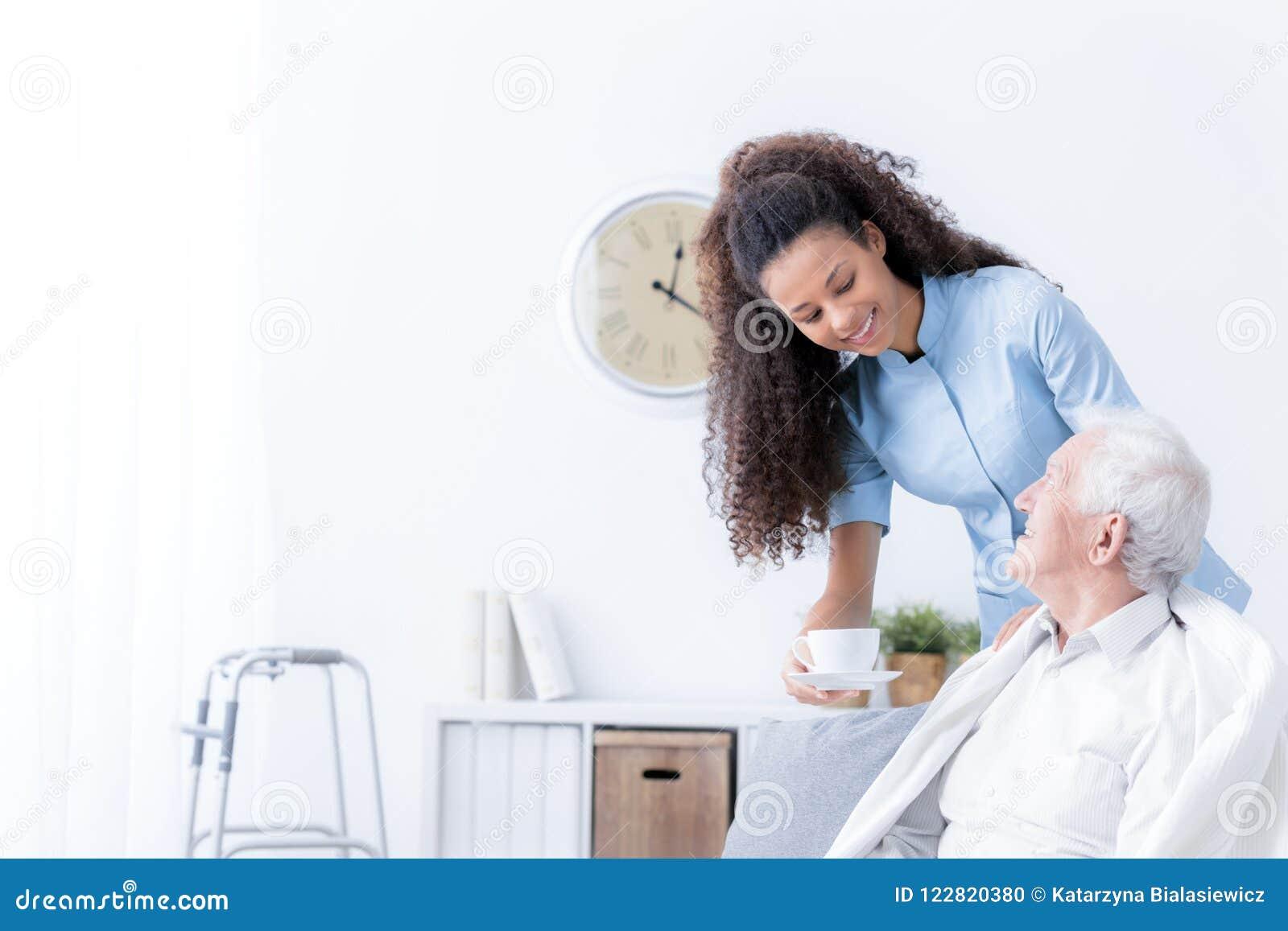 Glimlachende verpleegster die thee geven aan bejaarde in witte verzorgingshou