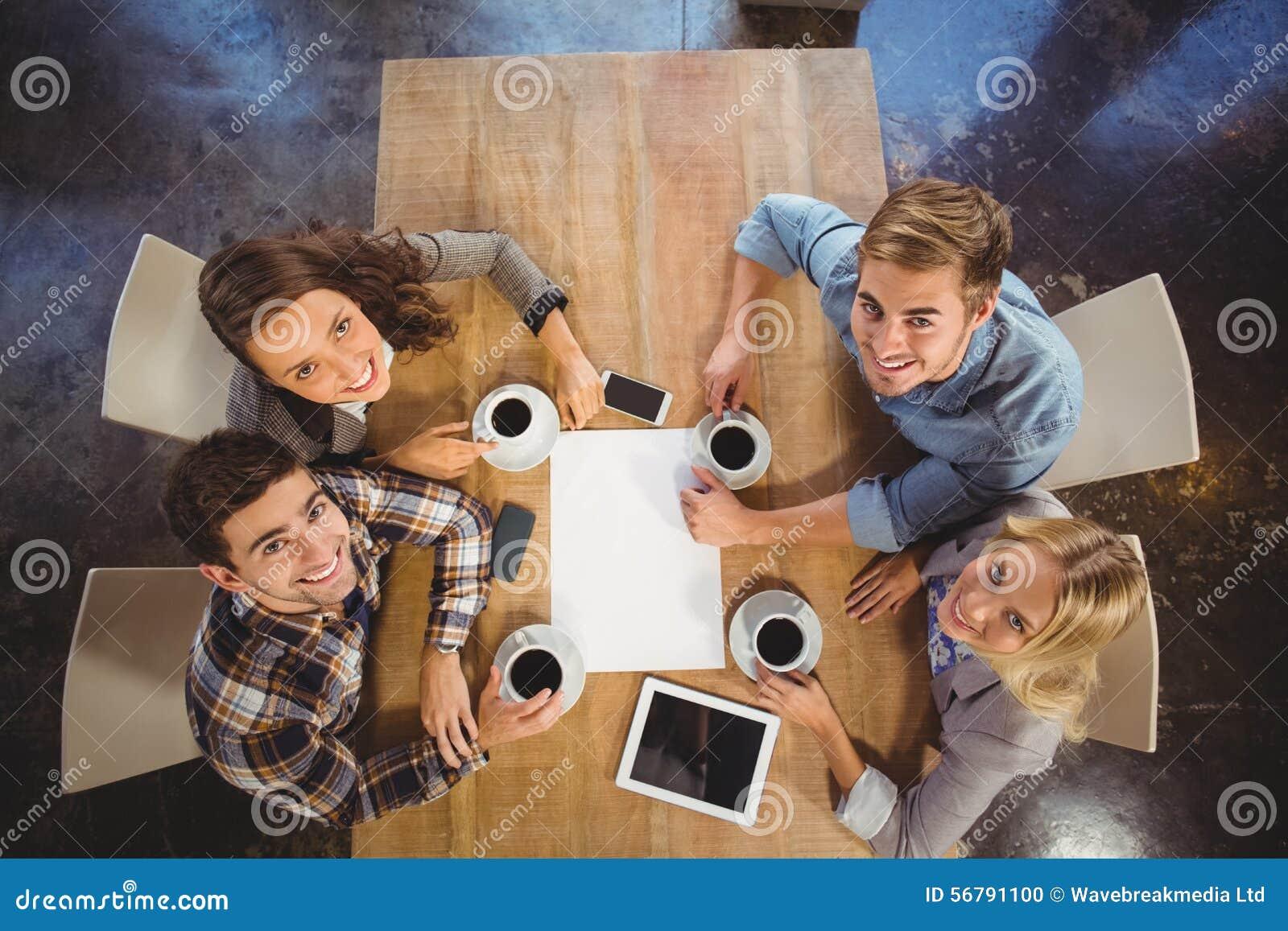 Glimlachende vrienden die en koffie zitten drinken