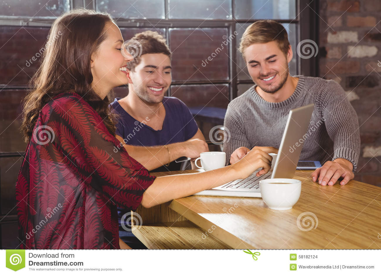 Glimlachende vrienden die koffie hebben samen en laptop bekijken