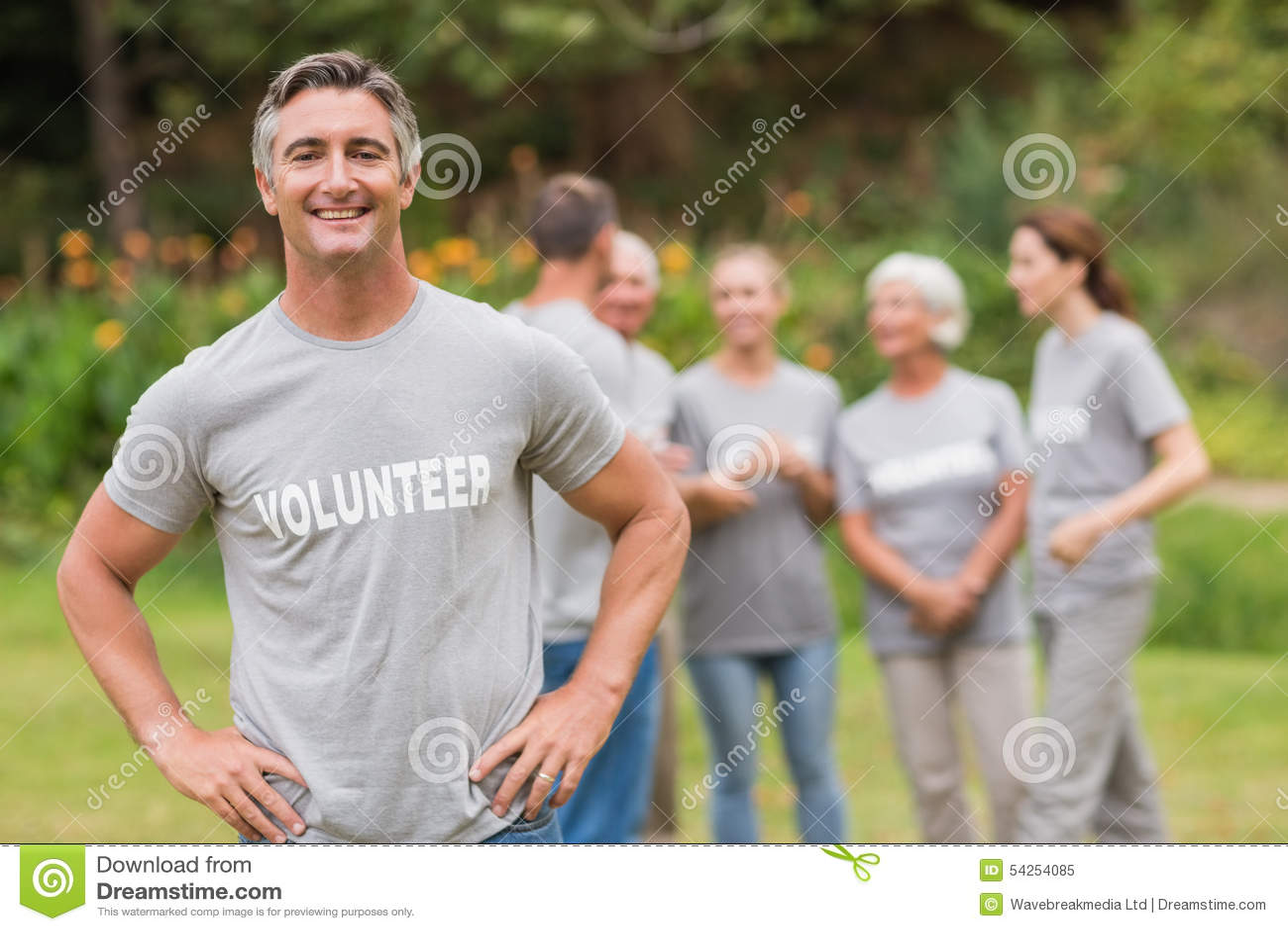 Glimlachende vrijwilliger die camera bekijken