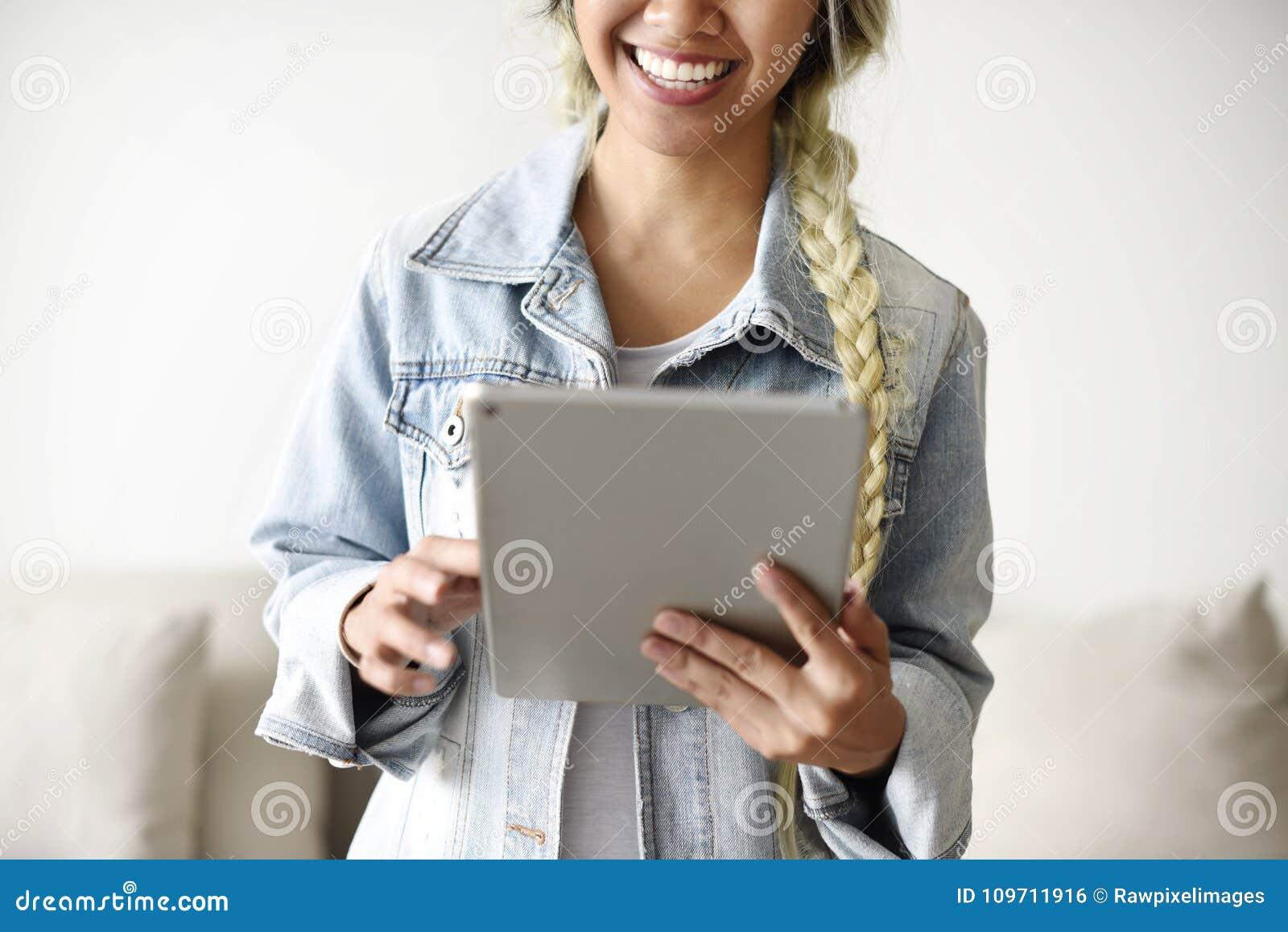 Glimlachende vrouw die een digitale tablet gebruiken