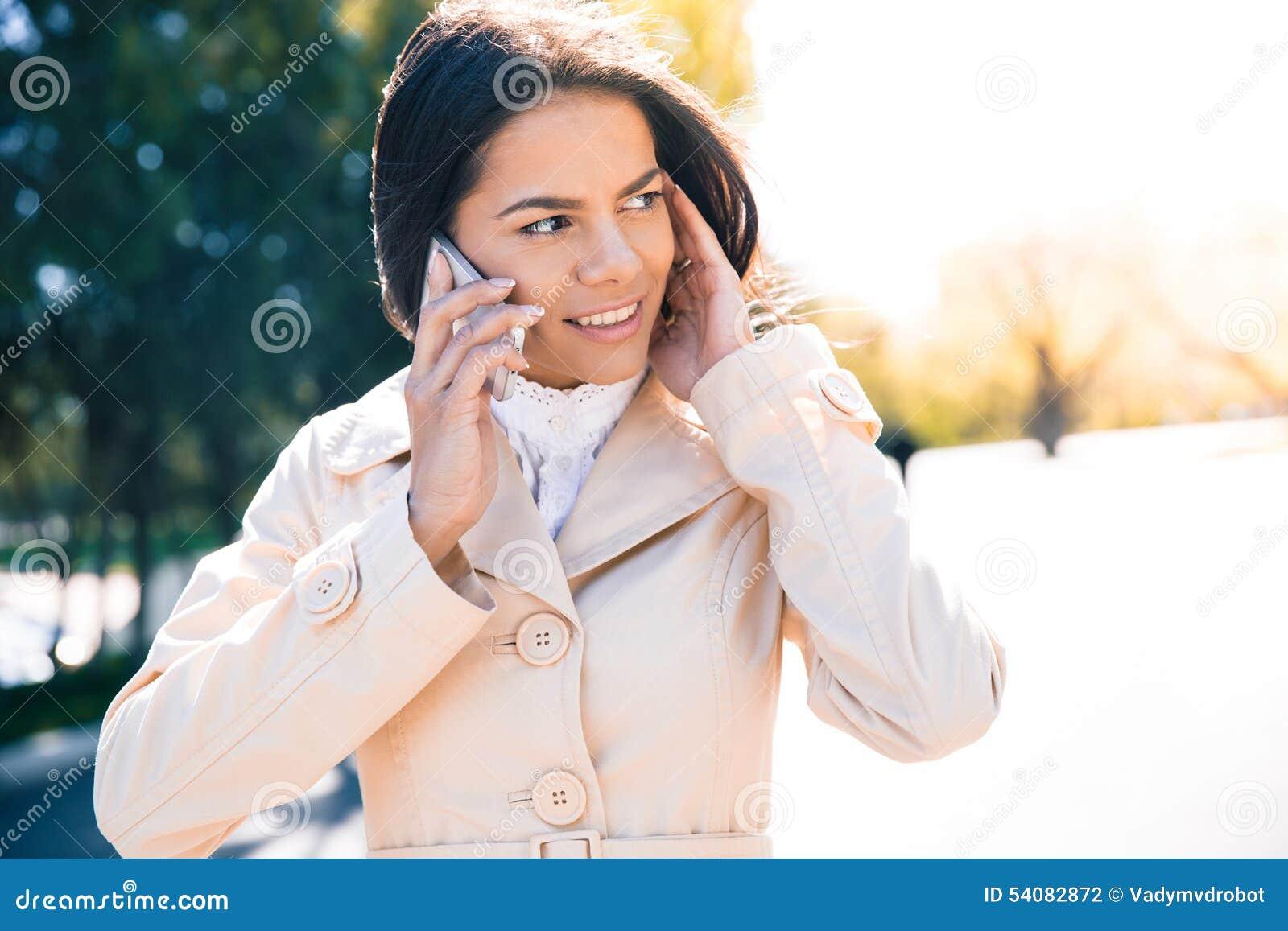 Glimlachende vrouw die op de telefoon spreekt