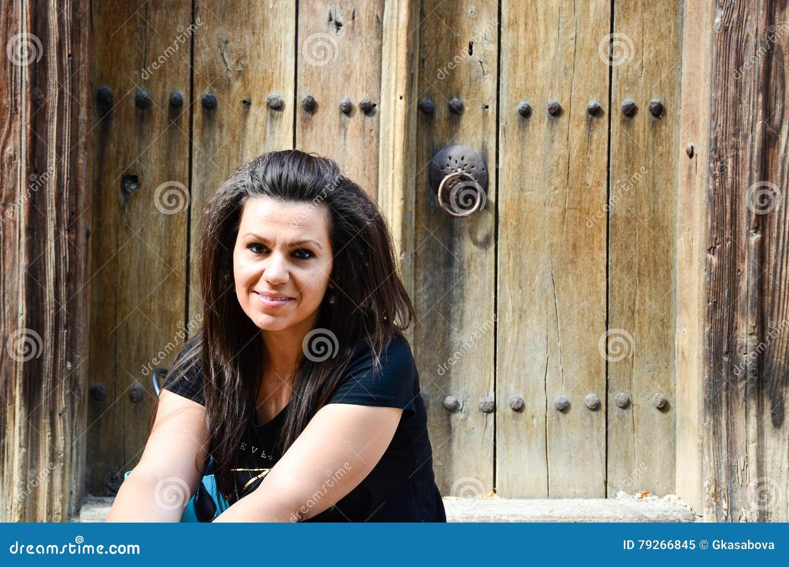 Glimlachende vrouw gezet voor oude deur
