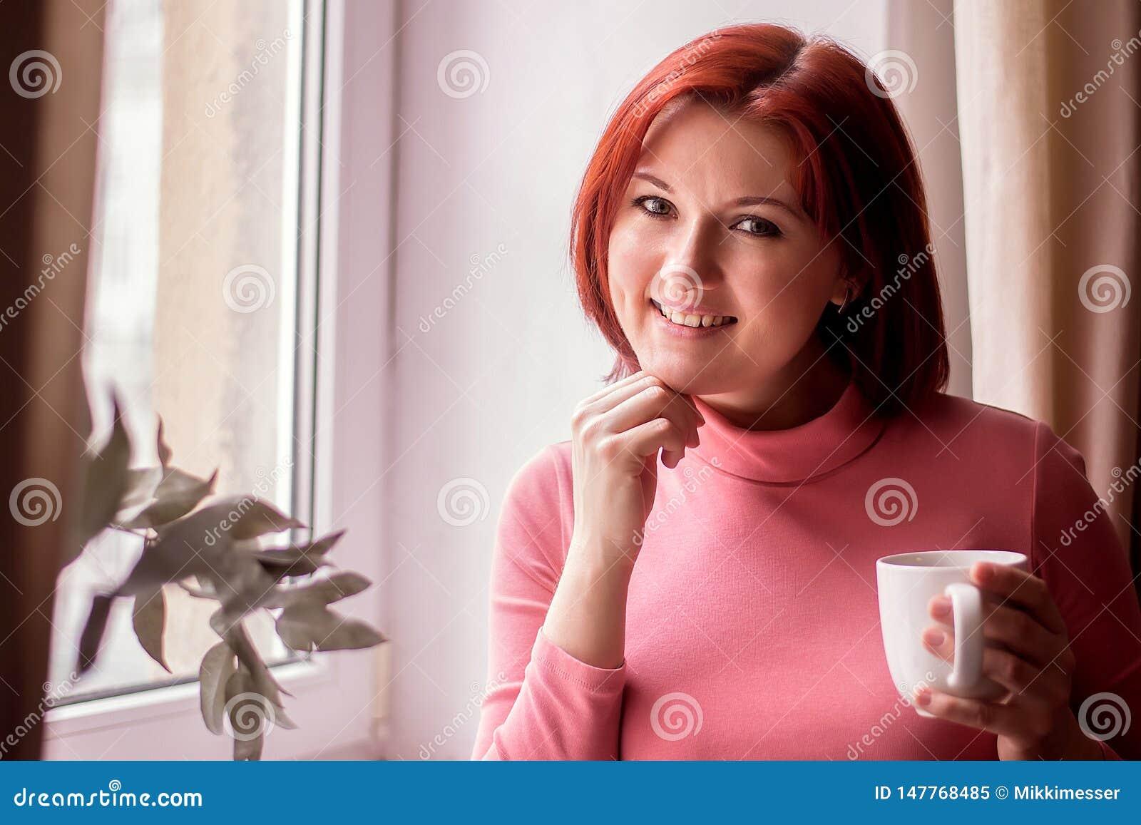 Glimlachende vrouw op middelbare leeftijd met rood haar die zich met witte mok dichtbij venster bevinden Kort koffiepauzeconcept